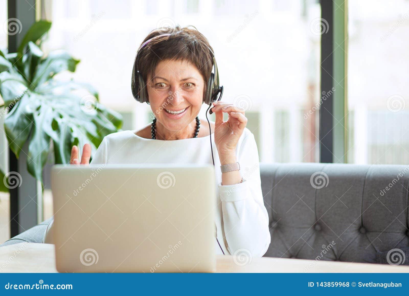 Сотрясенная зрелая женщина смотря компьютер