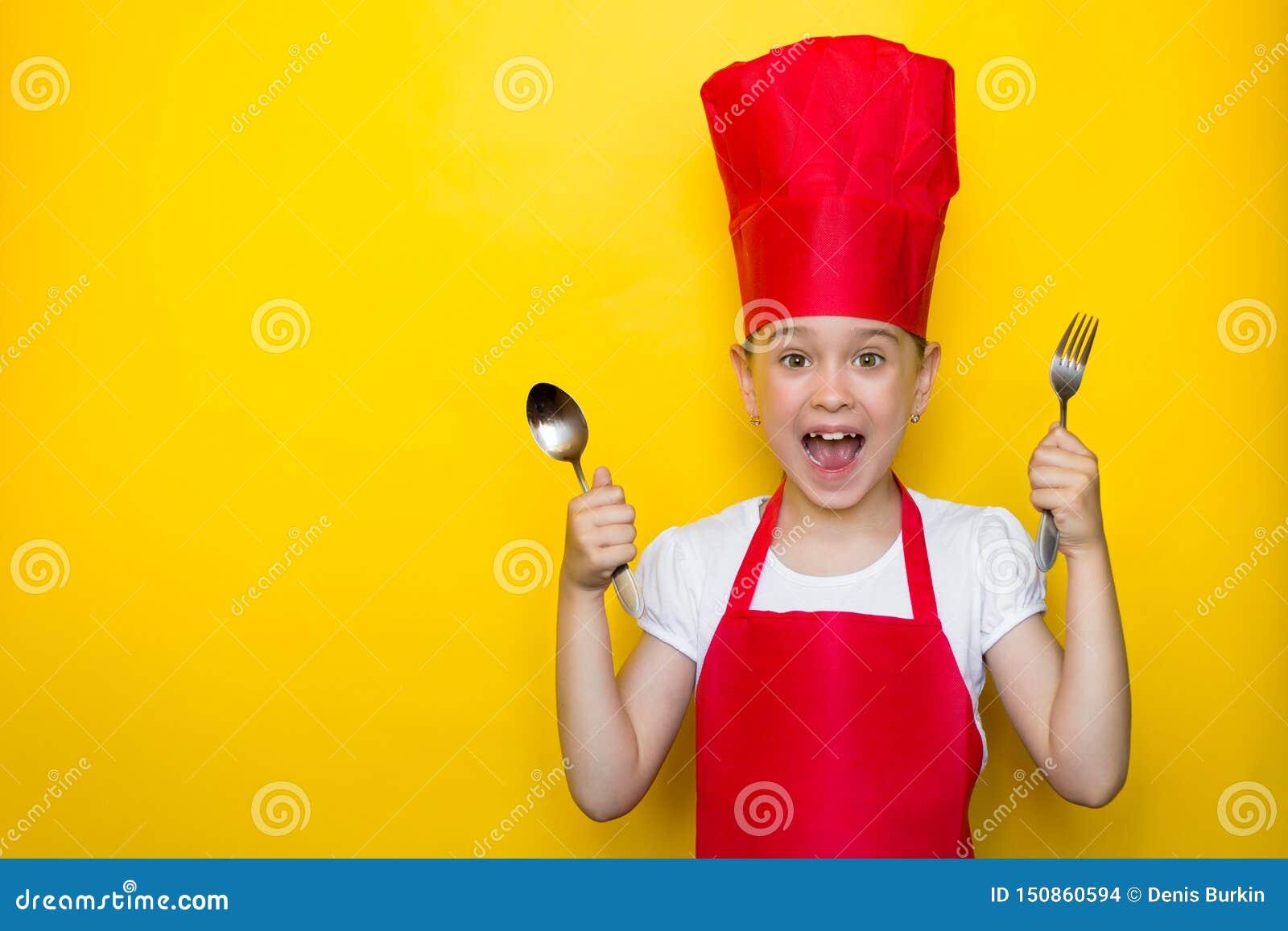 Сотрясенная и удивленная девушка кричащая в костюме красного шеф-повара держа ложку и вилку на желтой предпосылке с космосом экзе
