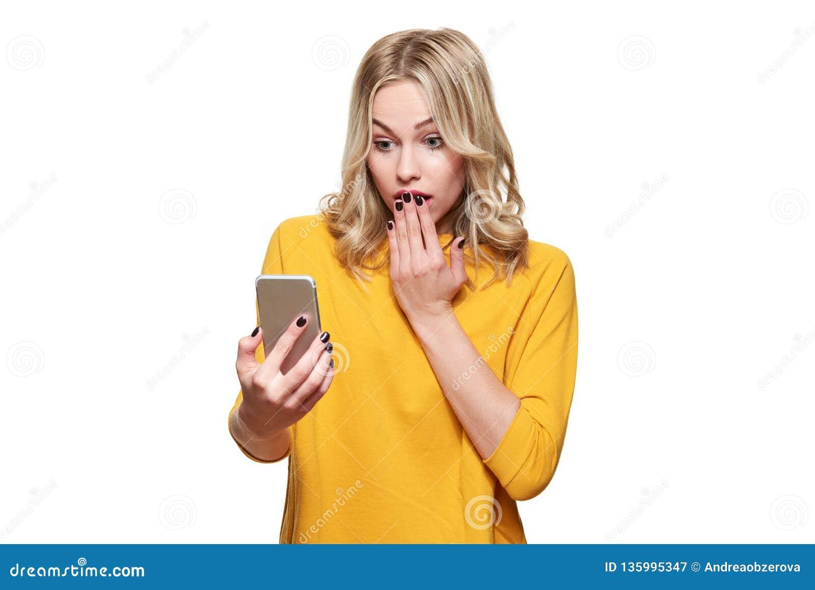 Сотрясенная молодая женщина задерживая ее мобильный телефон, читая сотрясая новости Женщина в неверии, изолированном над белой пр