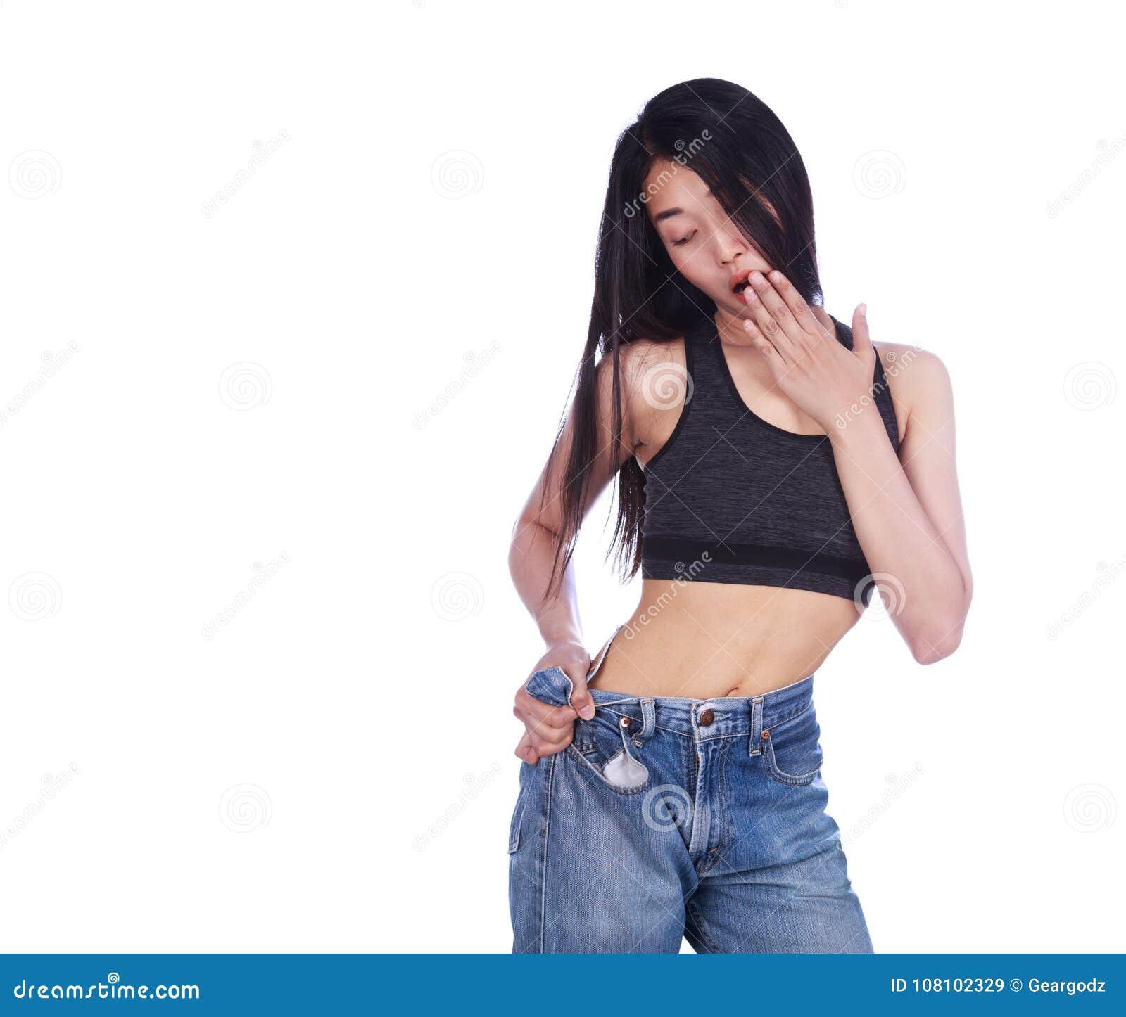 Сотрясенная тонкая женщина фитнеса в старых джинсах после проигрышного isol веса