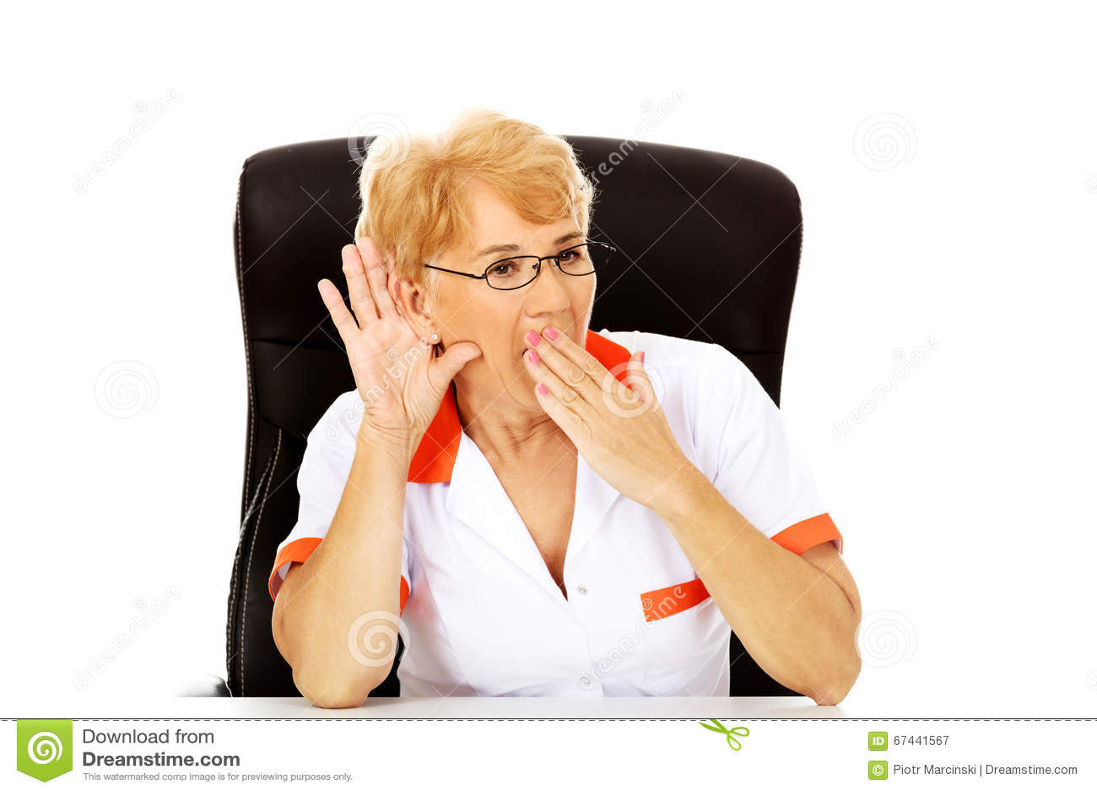 Сотрясенные пожилые женские доктор или медсестра сидя за столом и подслушивают переговор