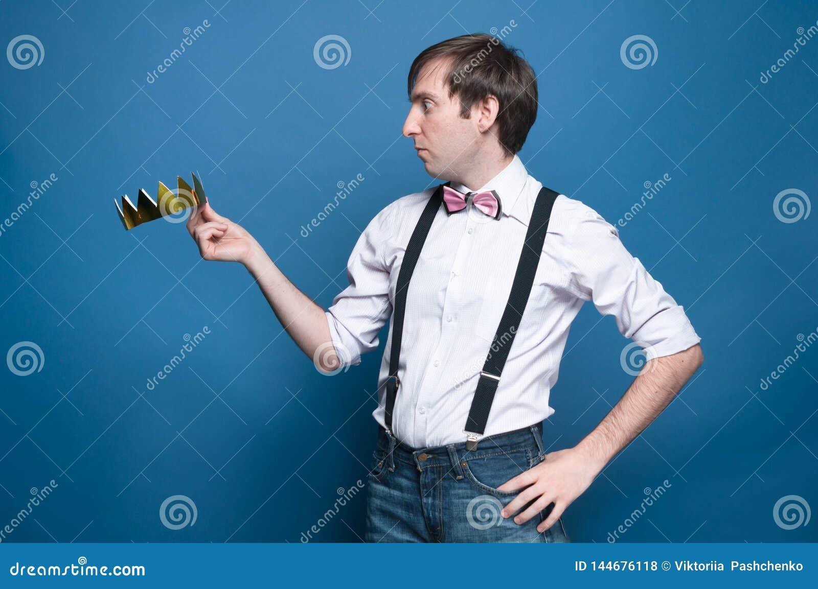 Сотрясенный красивый человек в рубашке, подтяжк, бабочке с рукой на бе