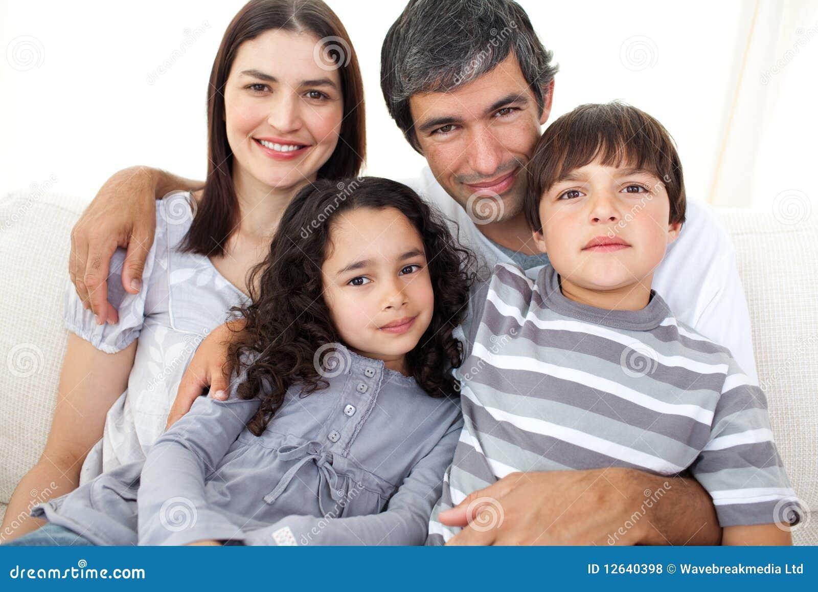софа любящего портрета семьи сидя