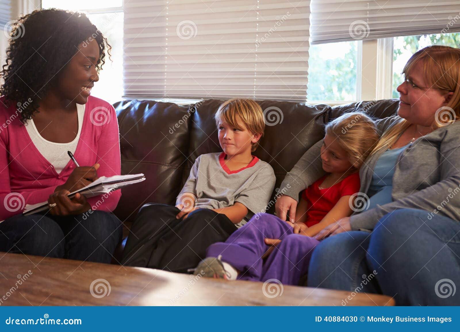 Социальный работник говоря к матери и детям дома