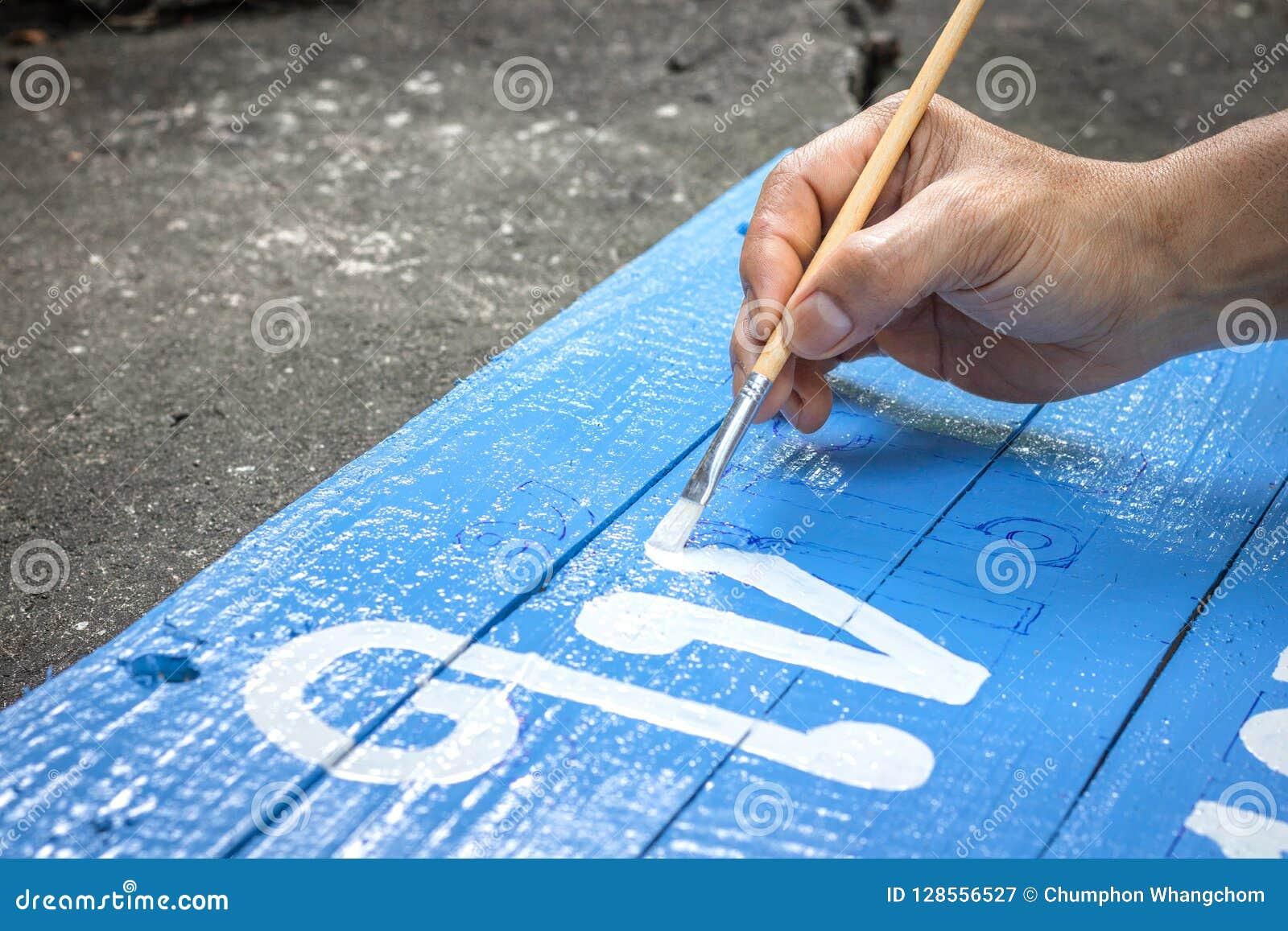 Сочинительство человека подписывает доску с щеткой акварелей на предпосылке пола цемента Картина на деревянной доске в тайском яз