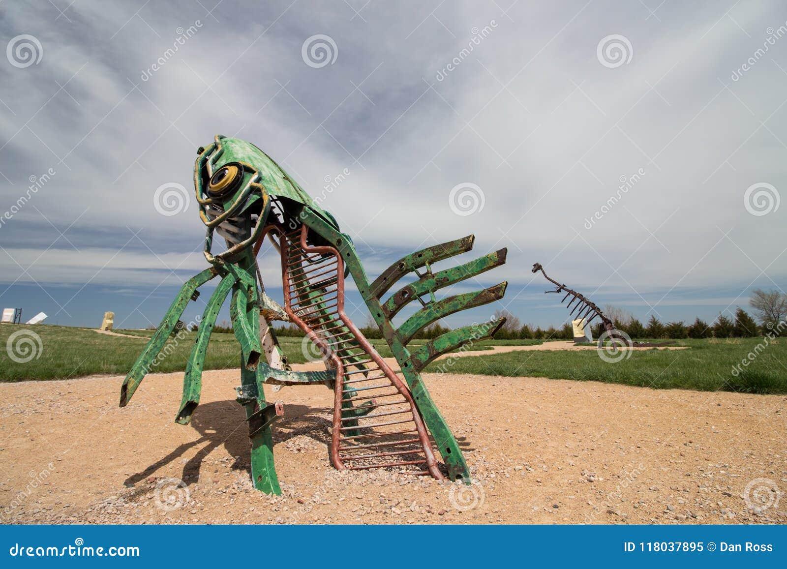 Союзничество, Nebraska/USA - 8-ое мая 2018: Специфическая скульптура металла рыбы перескакивая из земли в Небраске