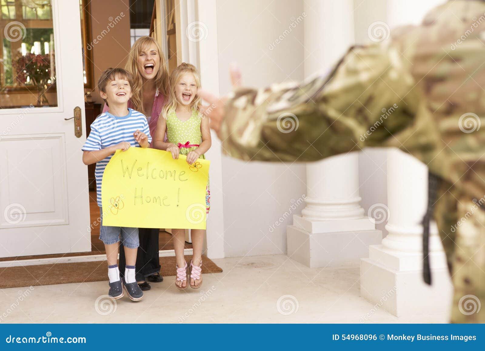 Солдат возвращающ домой и приветствованный семьей