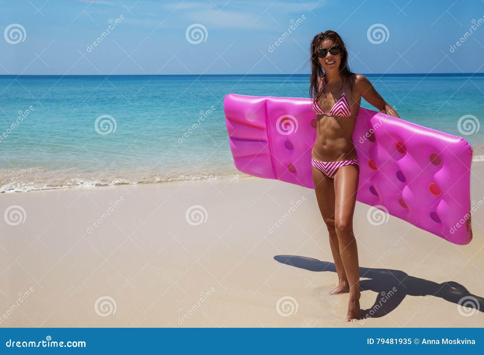 Солнечные очки женщины брюнет загорают с тюфяком воздуха на троповом пляже
