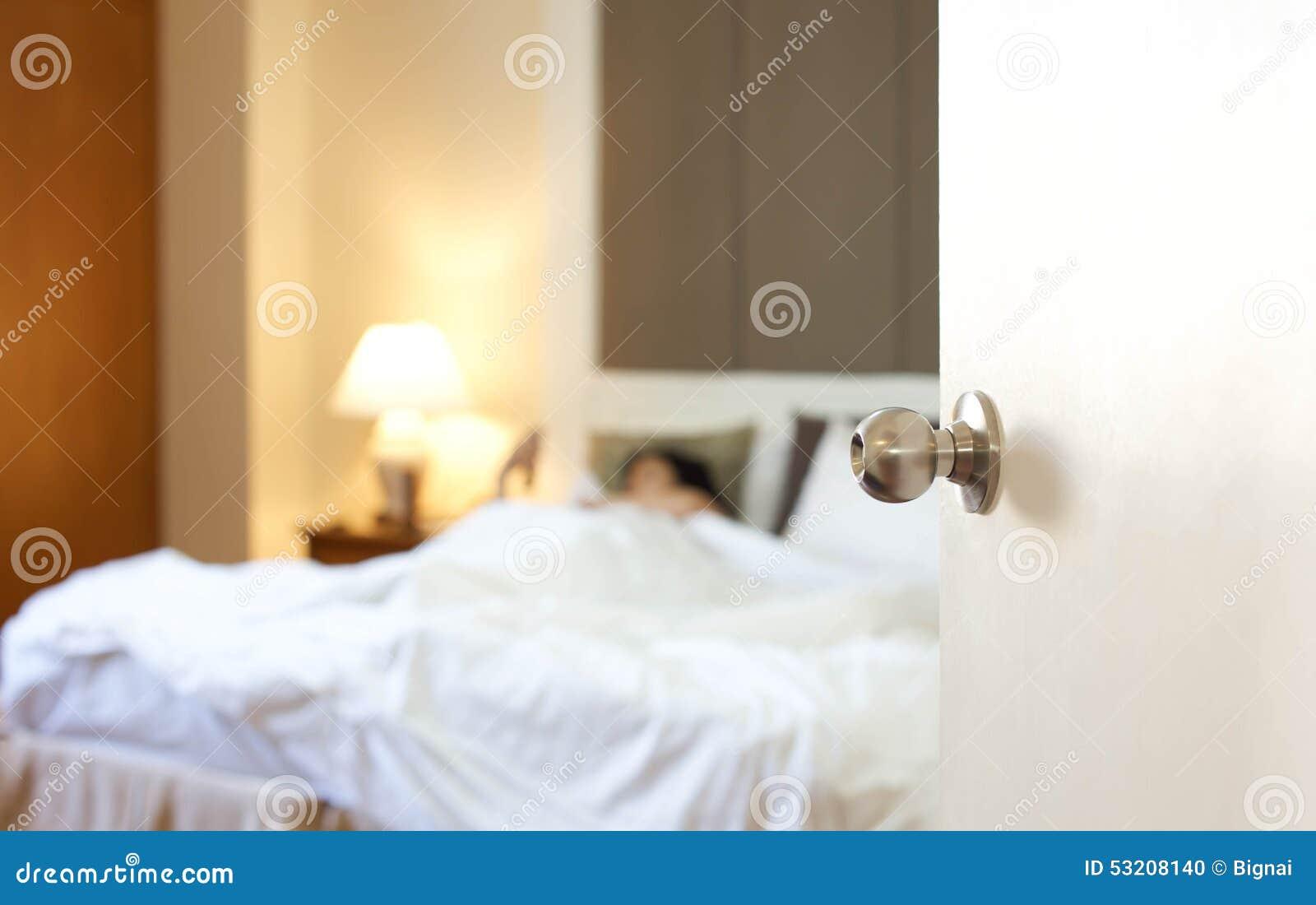 Спать женщина отдыхая в кровати с дверью раскрывает