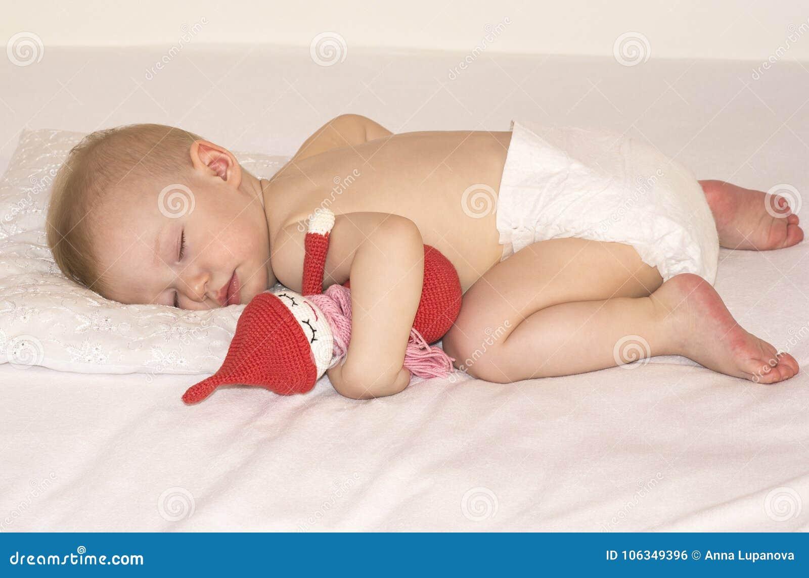 Спать младенец в пеленке с handmade игрушкой