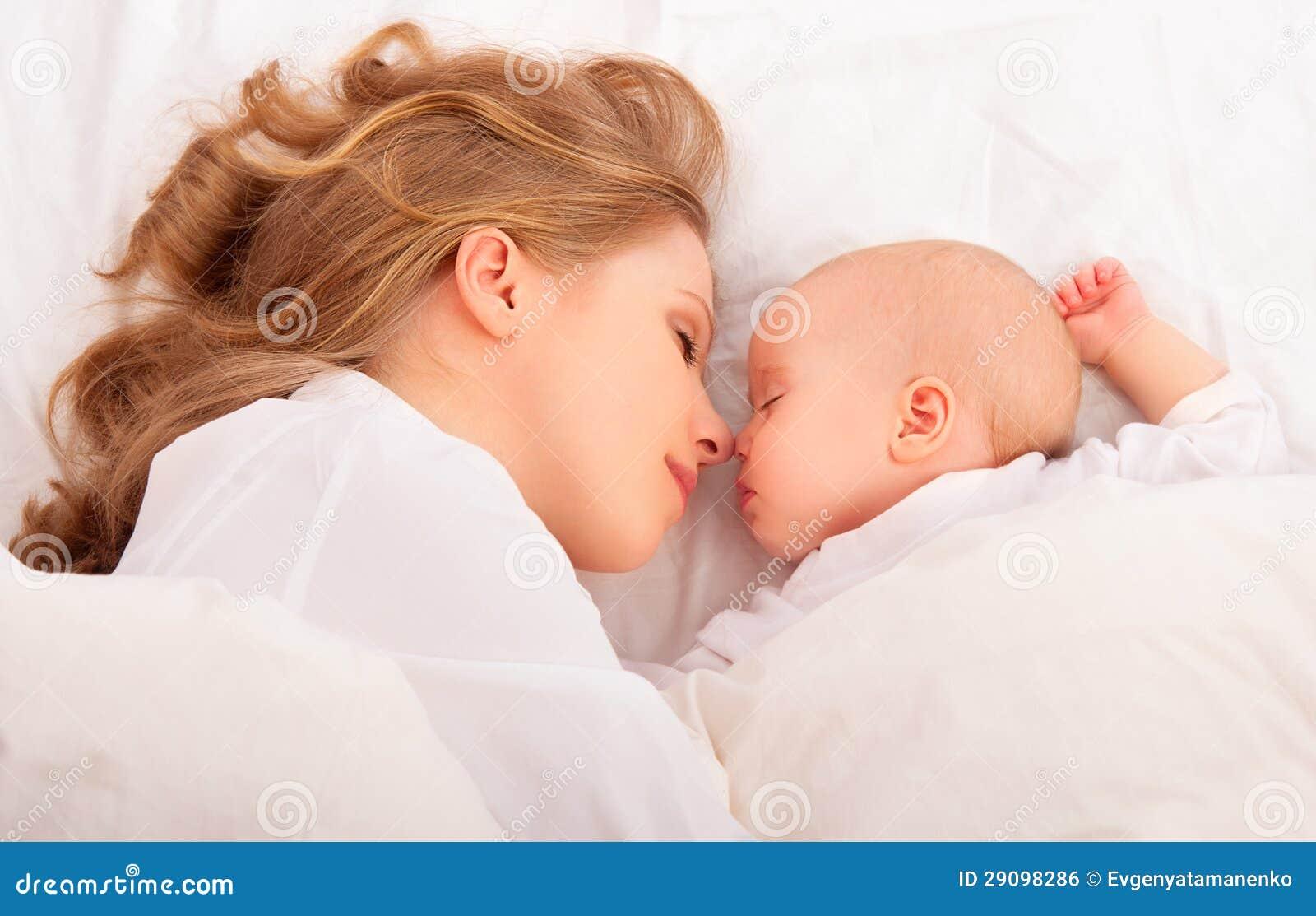 Спать совместно. мать обнимает newborn младенца в кровати