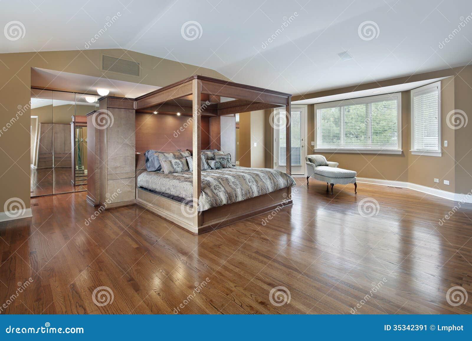 Спальня хозяев с кроватью обрамленной древесиной