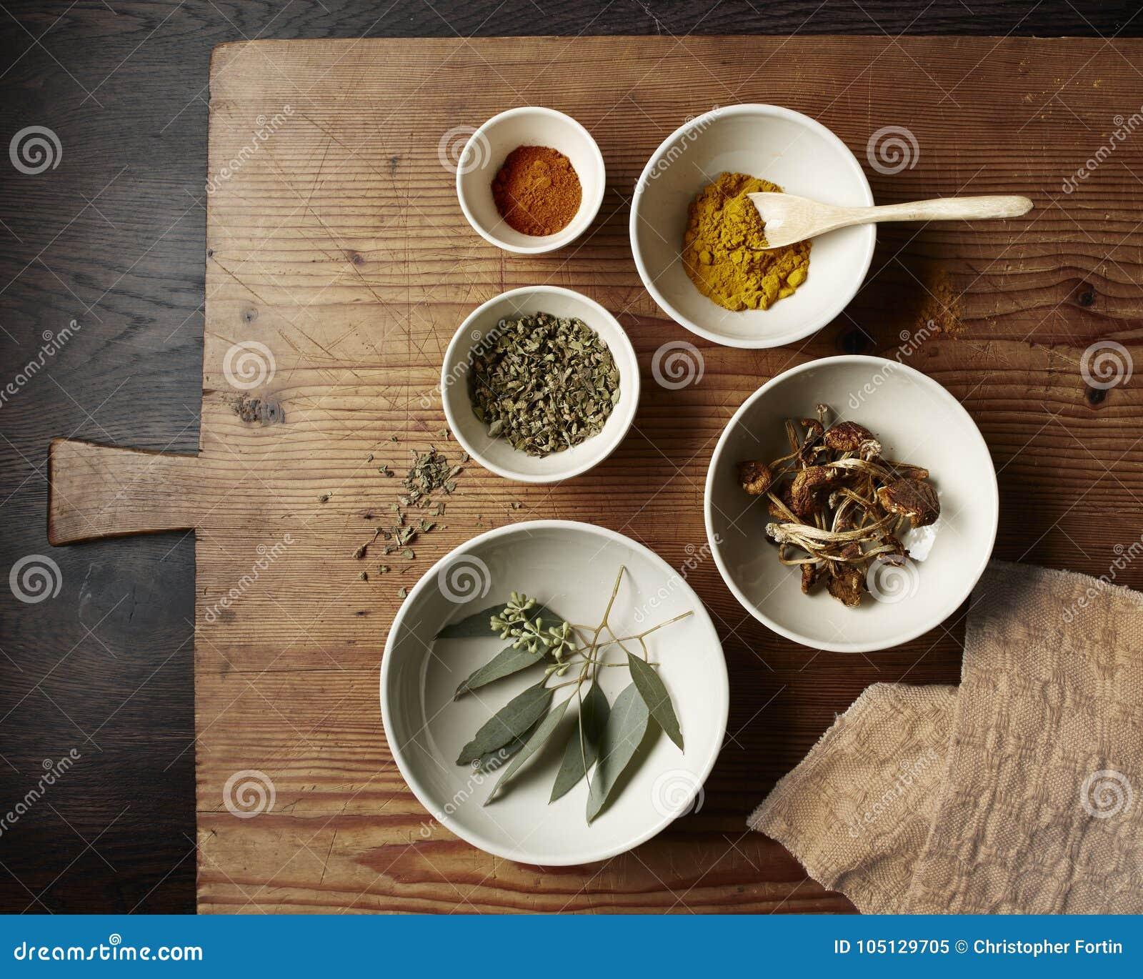Специи, грибы и листья в белых шарах на деревенской деревянной разделочной доске