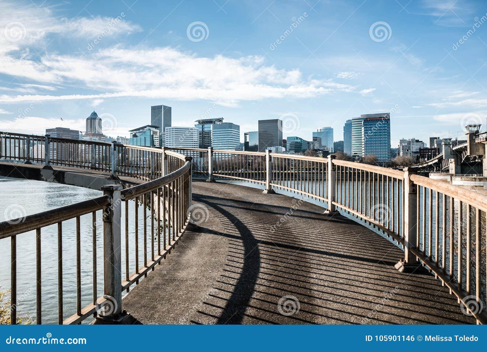 Спиральный пешеходный мост обозревая реку Willamette и городской горизонт города в Портленде, Орегоне декабре 2017