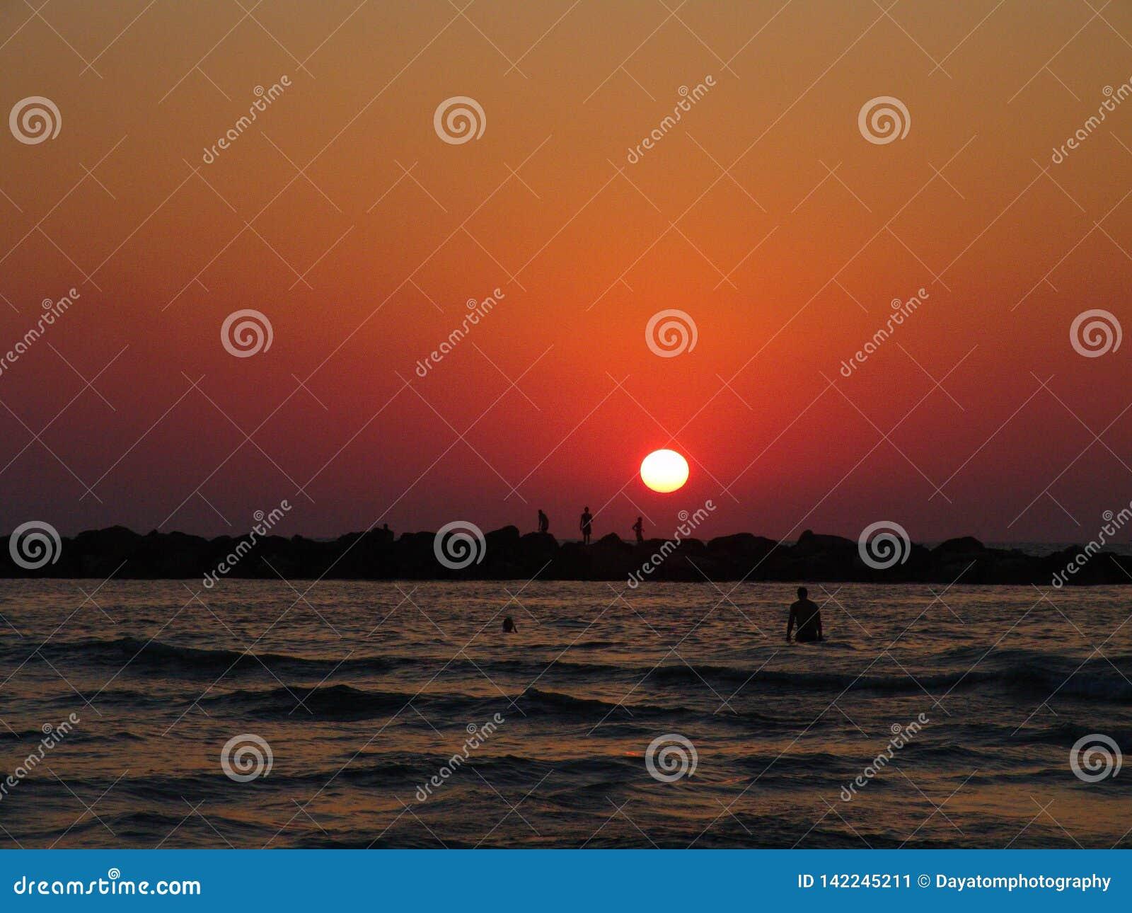 Спокойный заход солнца лета над пляжем моря Тель-Авив, в ярких оранжевых цветах с силуэтами людей плавая, удя и идя дальше