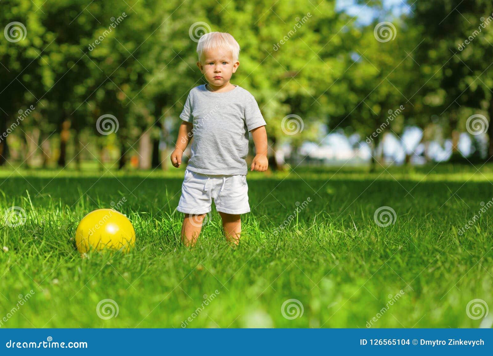 Спокойный ребенк играя с шариком снаружи