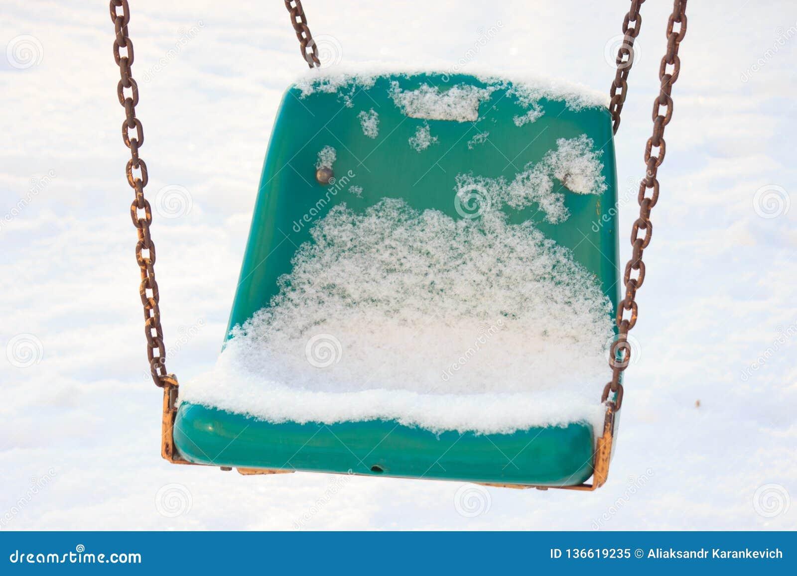 Спортивная площадка детей в зиме, качаниях и carousels под снегом на солнечный день отсутствие людей, пустой области, ждать