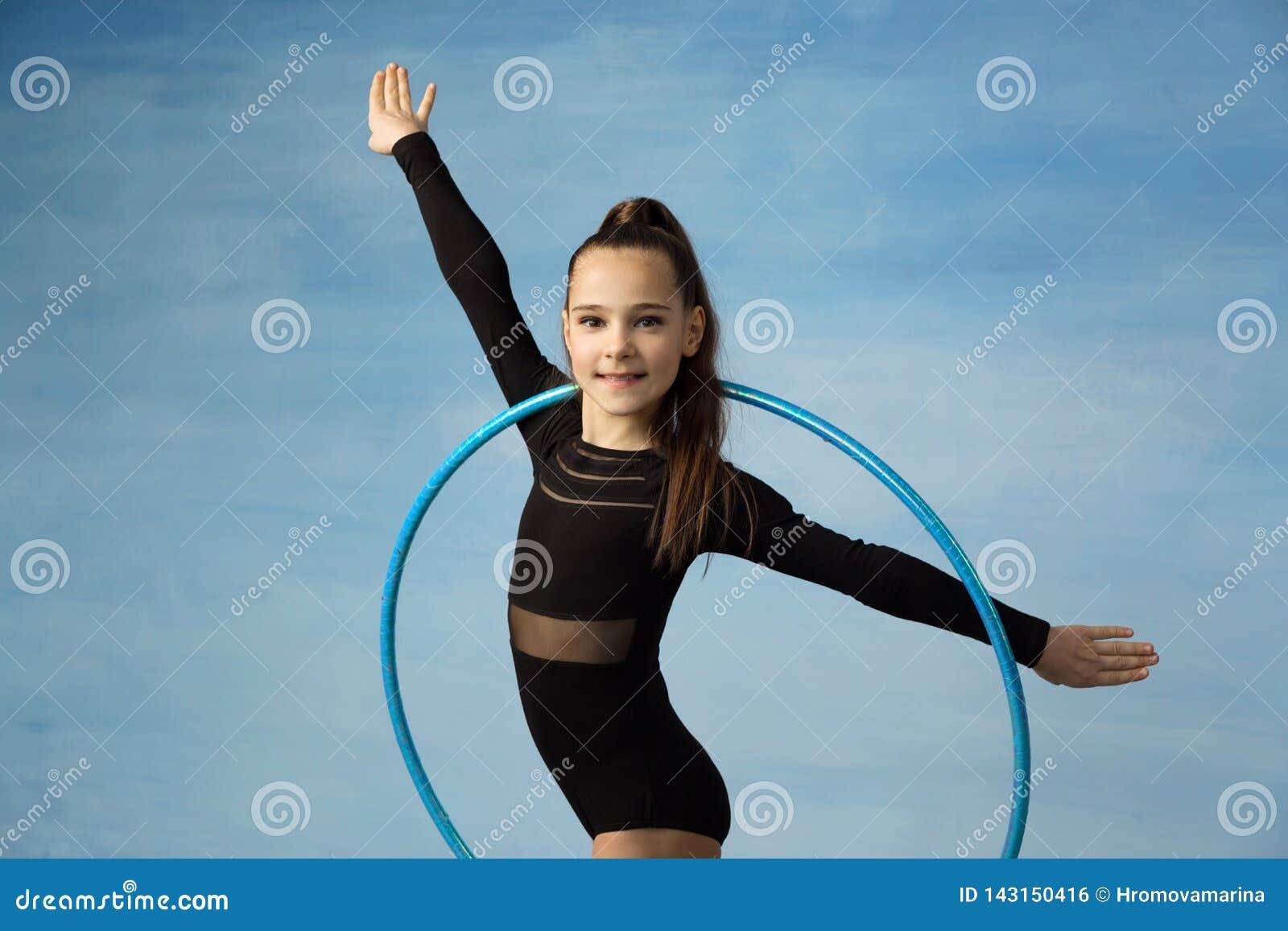 Спортсмен девушки делая гимнастику тренировки, смотря камеру делая тренировку с обручем