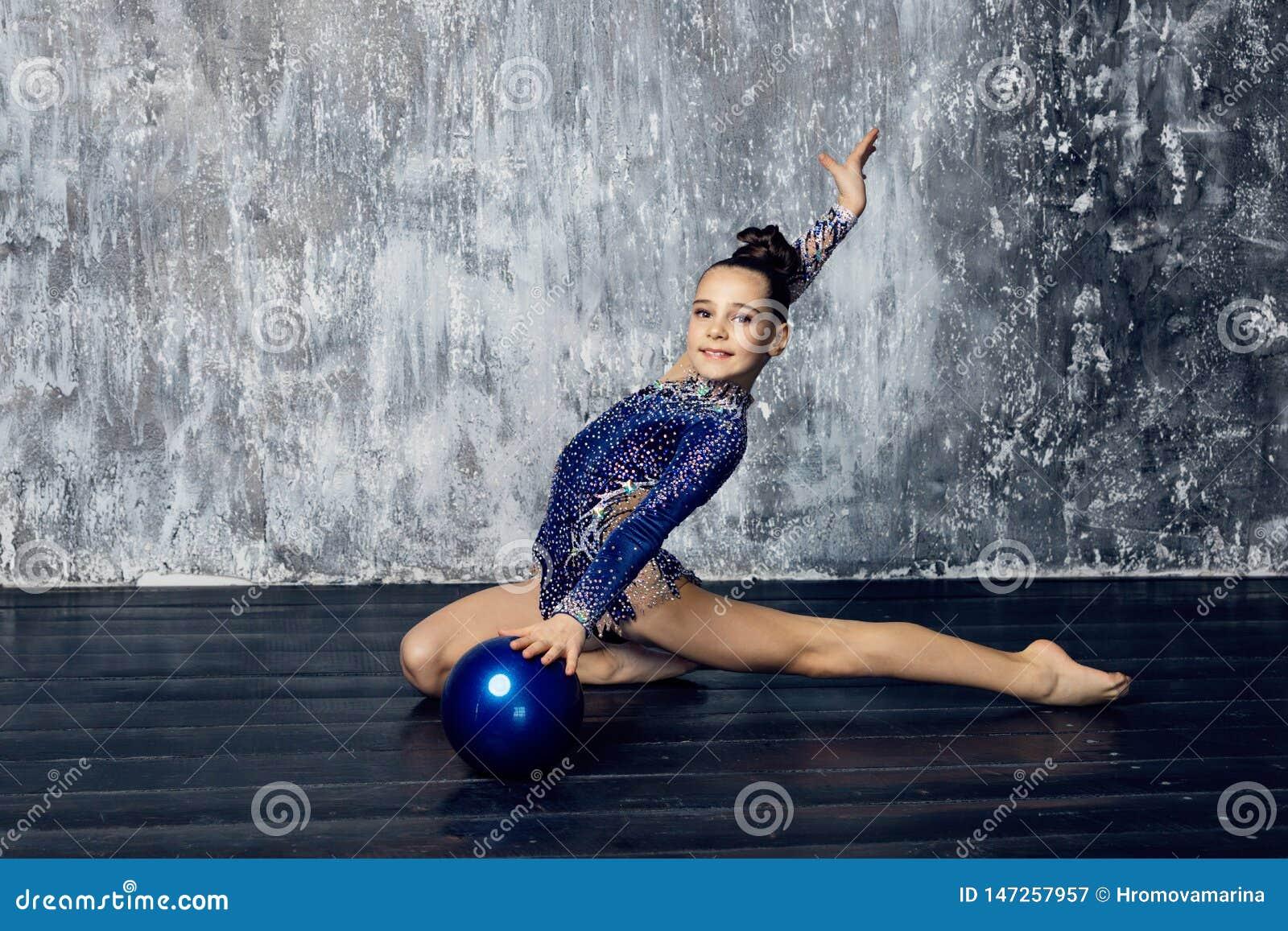 Спортсмен девушки звукомерное гимнастическое в голубом костюме со сверкнает делает тренировку с шариком спорт