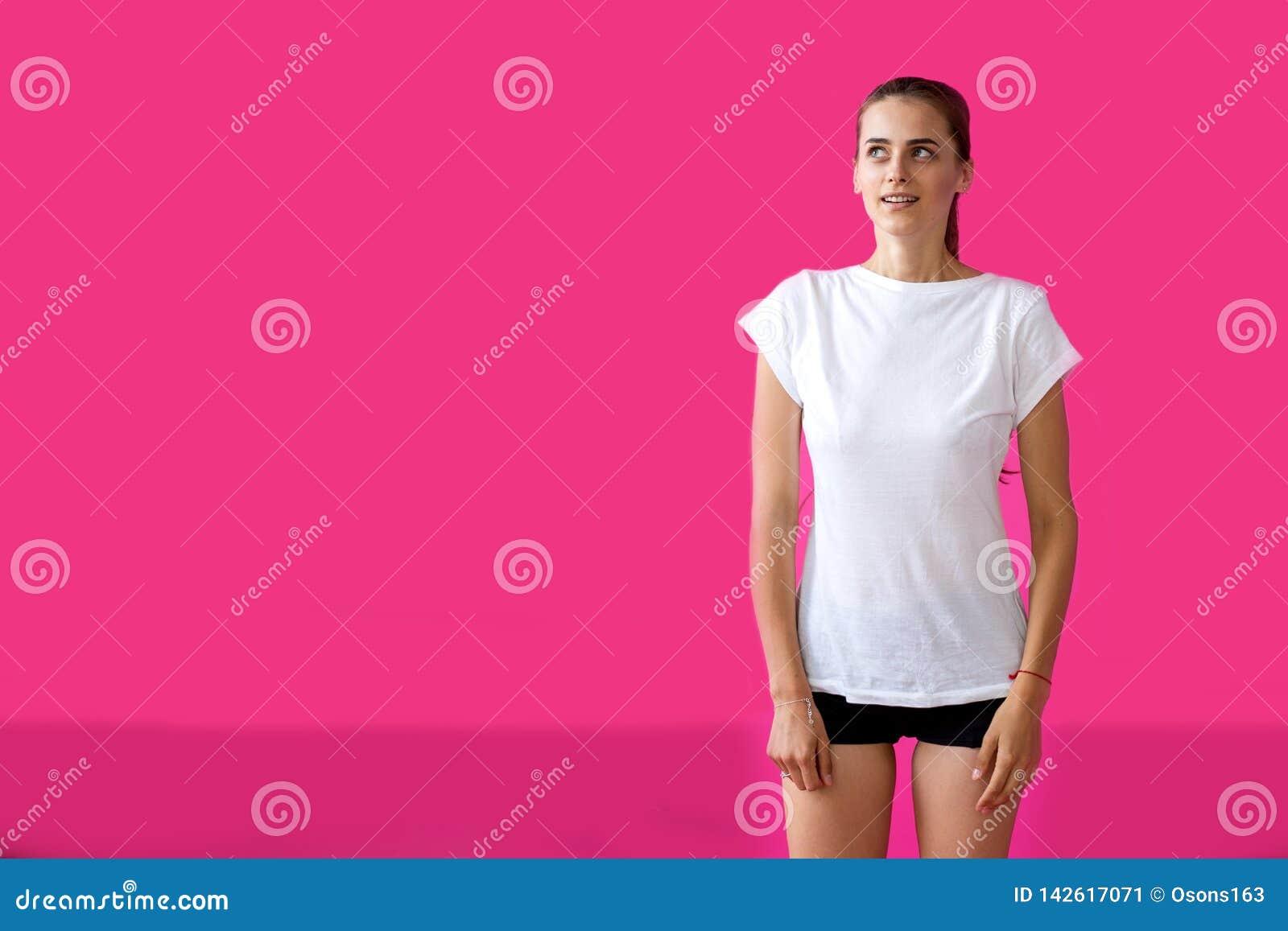 Спортсмен девушки представляя на розовой предпосылке