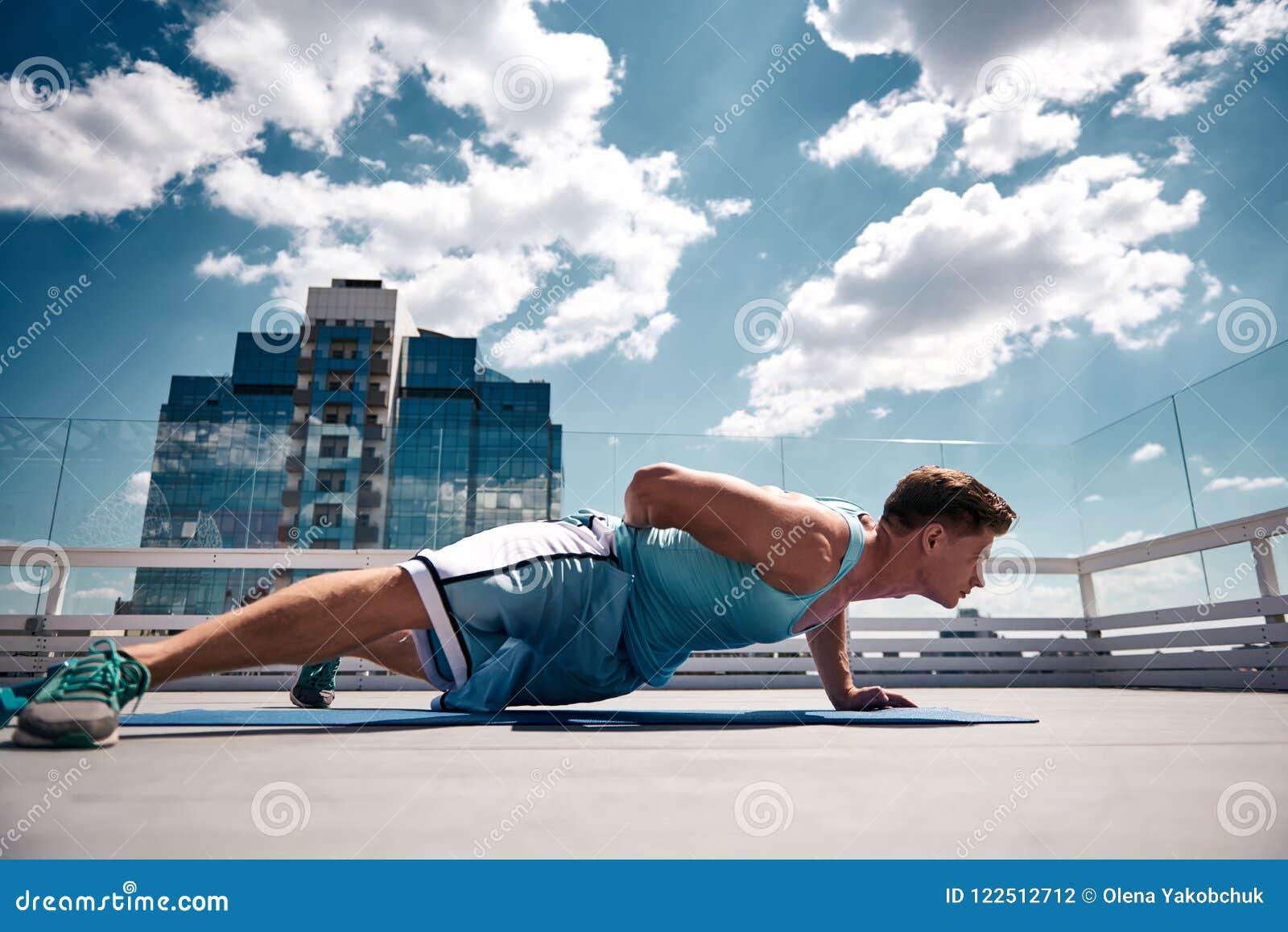 Спортсмен делает нажим-поднимает на высокой террасе