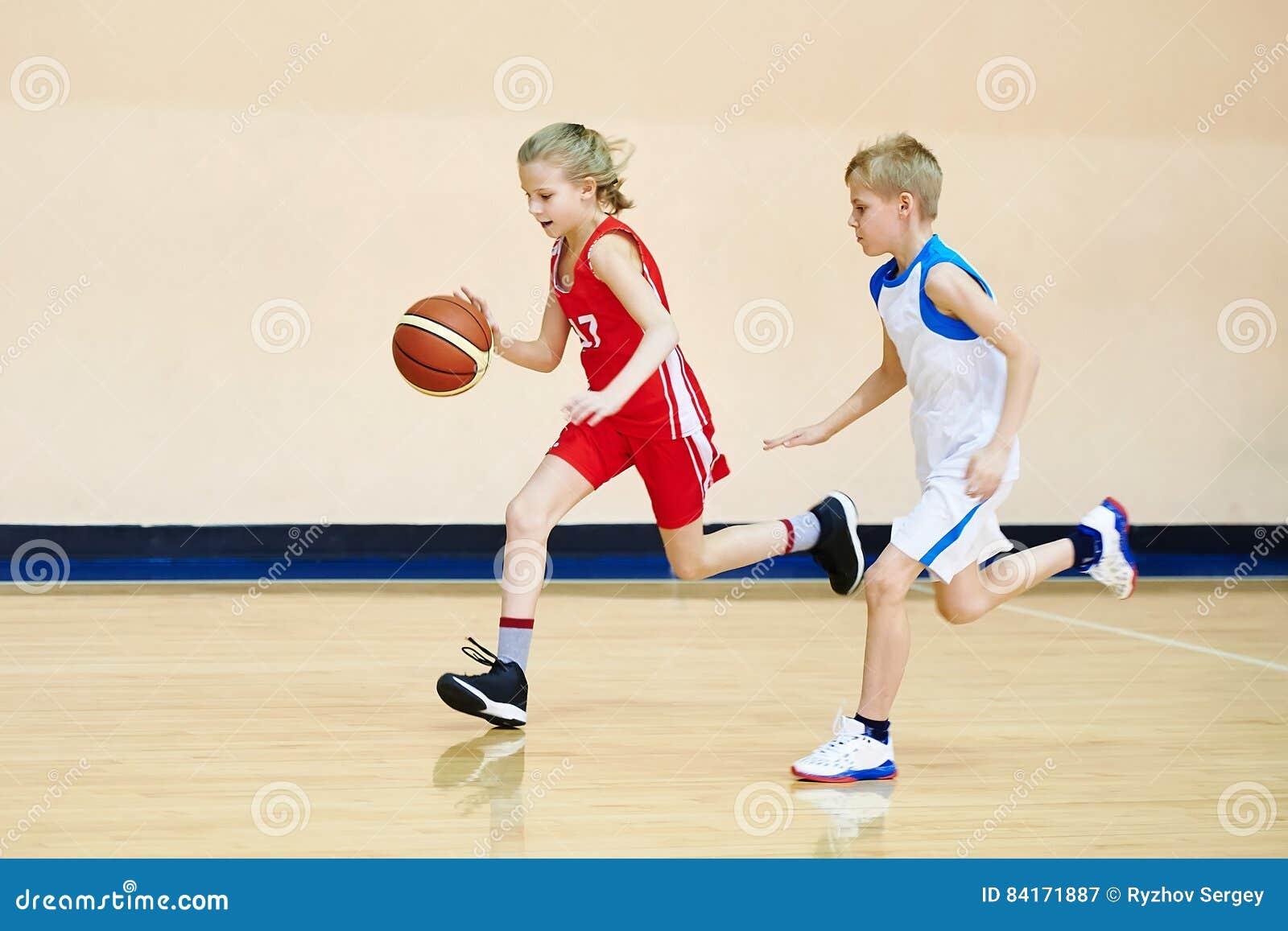 Спортсмен девушки и мальчика в форме играя баскетбол