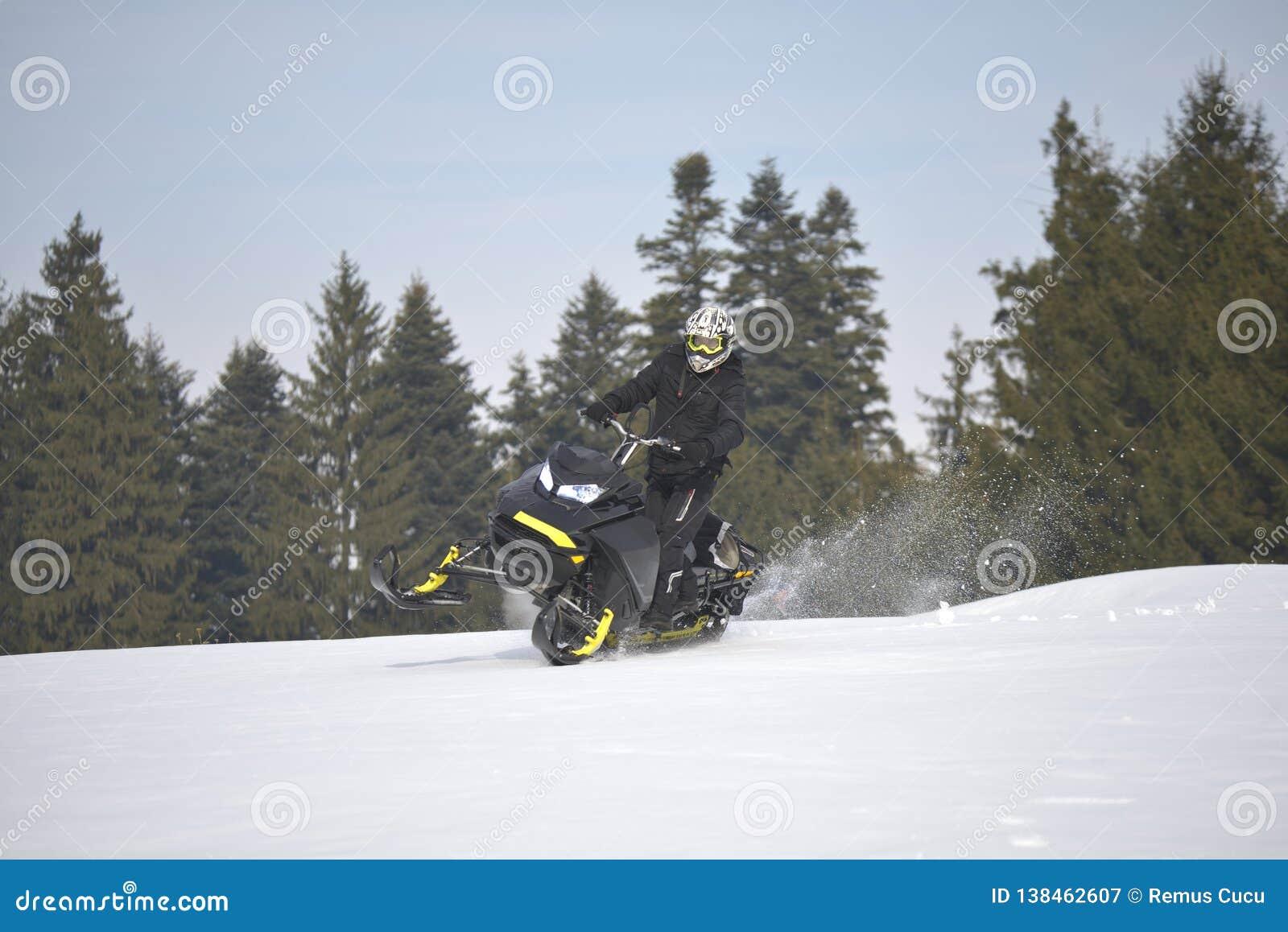 Спортсмен на снегоходе двигая в лес зимы в горах