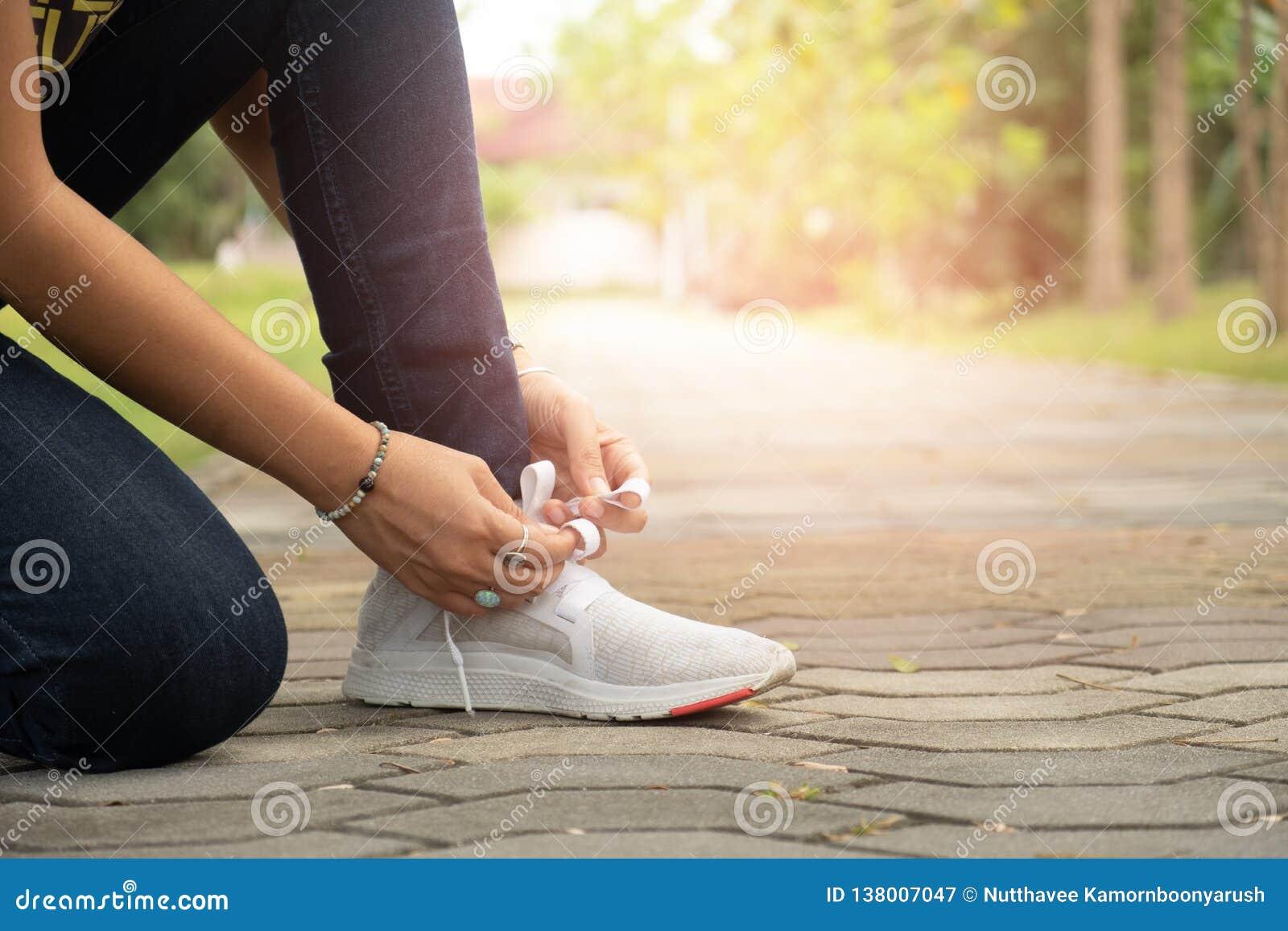 Спортсмен сидит вниз к веревочке ботинка