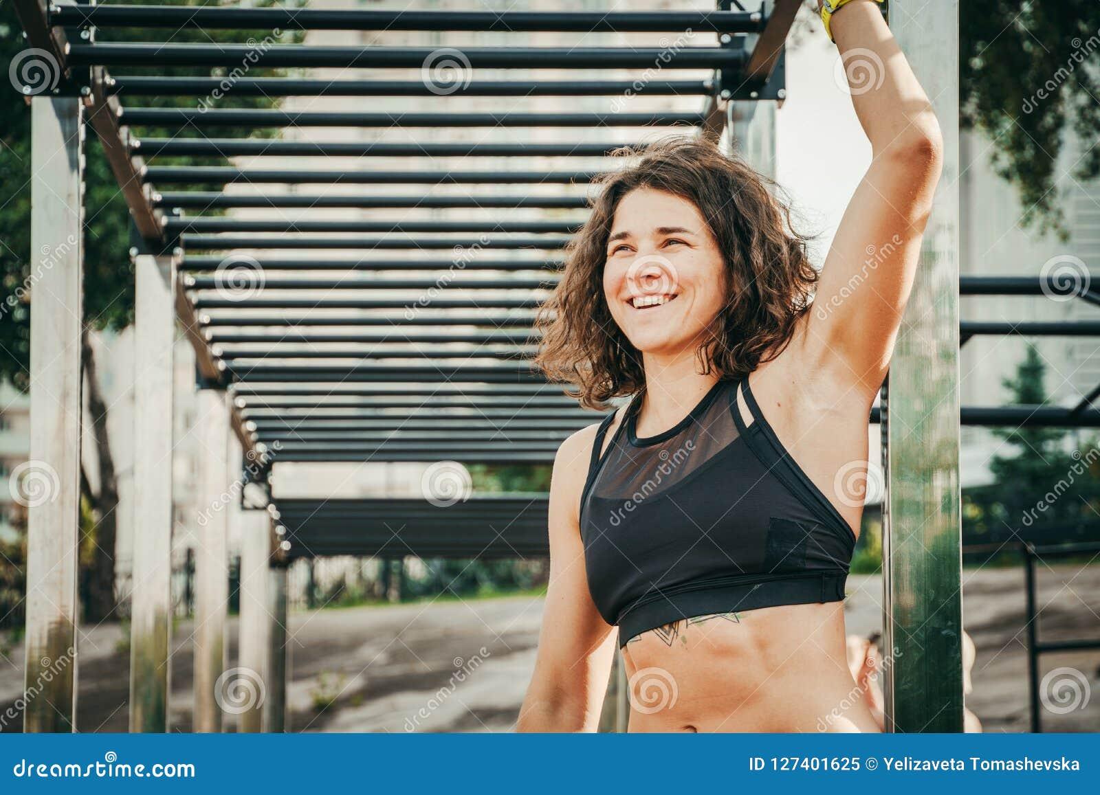 Спорт и здоровье женщин темы Красивая кавказская женщина с курчавыми длинными волосами представляя на hor удерживания земли на от