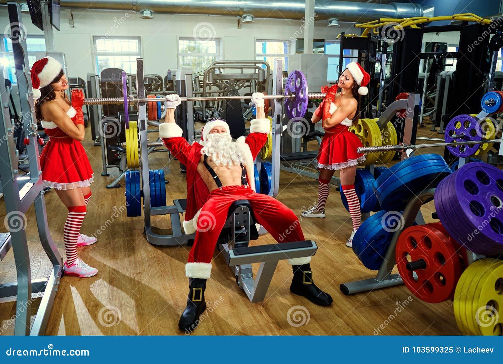 Спорт Санта Клаус с девушками в костюмах ` s Санты в спортзале дальше