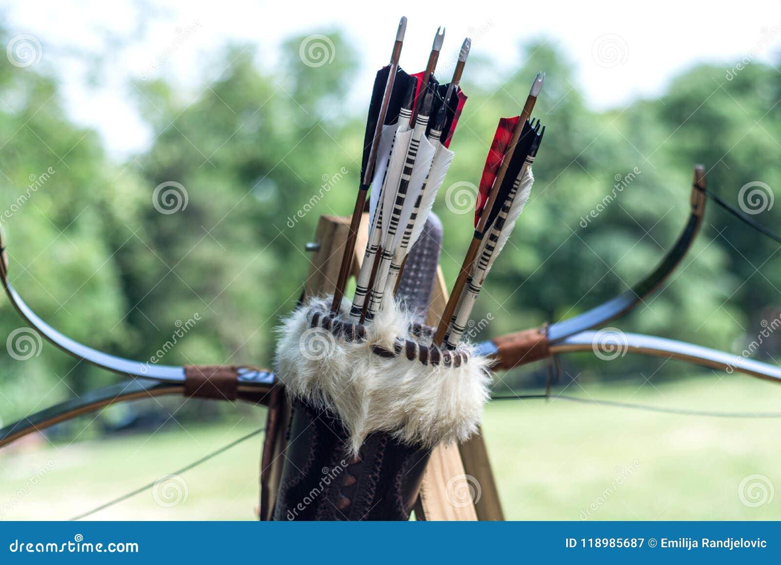 Средневековый комплект старых деревянных стрелок в кожаном случае и смычков вися на стойке