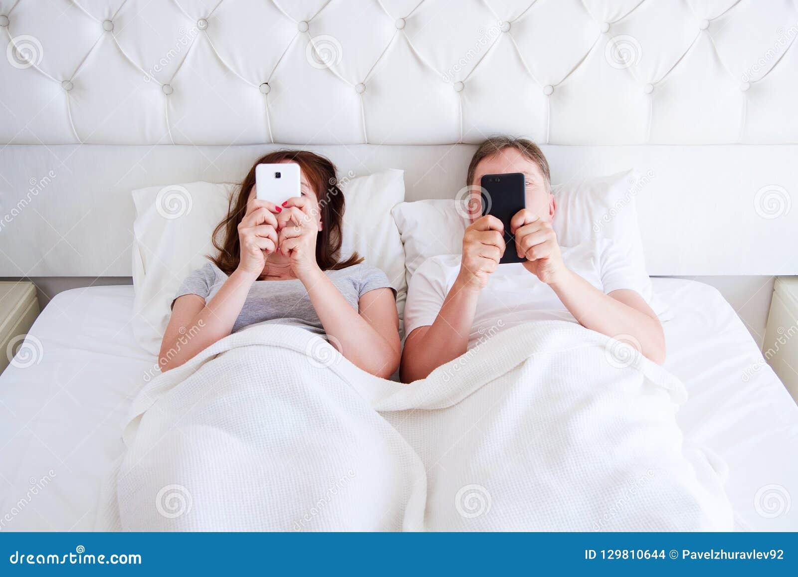 Средние достигшие возраста мобильные телефоны в спальне, современная концепция владением пар людей