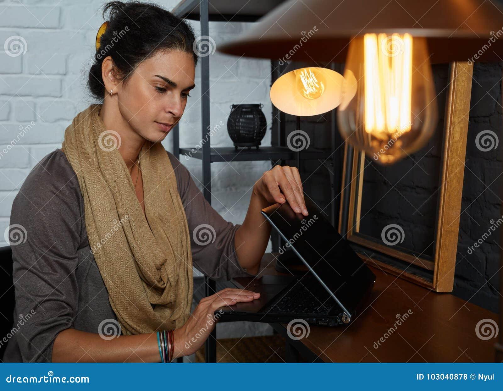 Средняя взрослая женщина работая с компьтер-книжкой дома