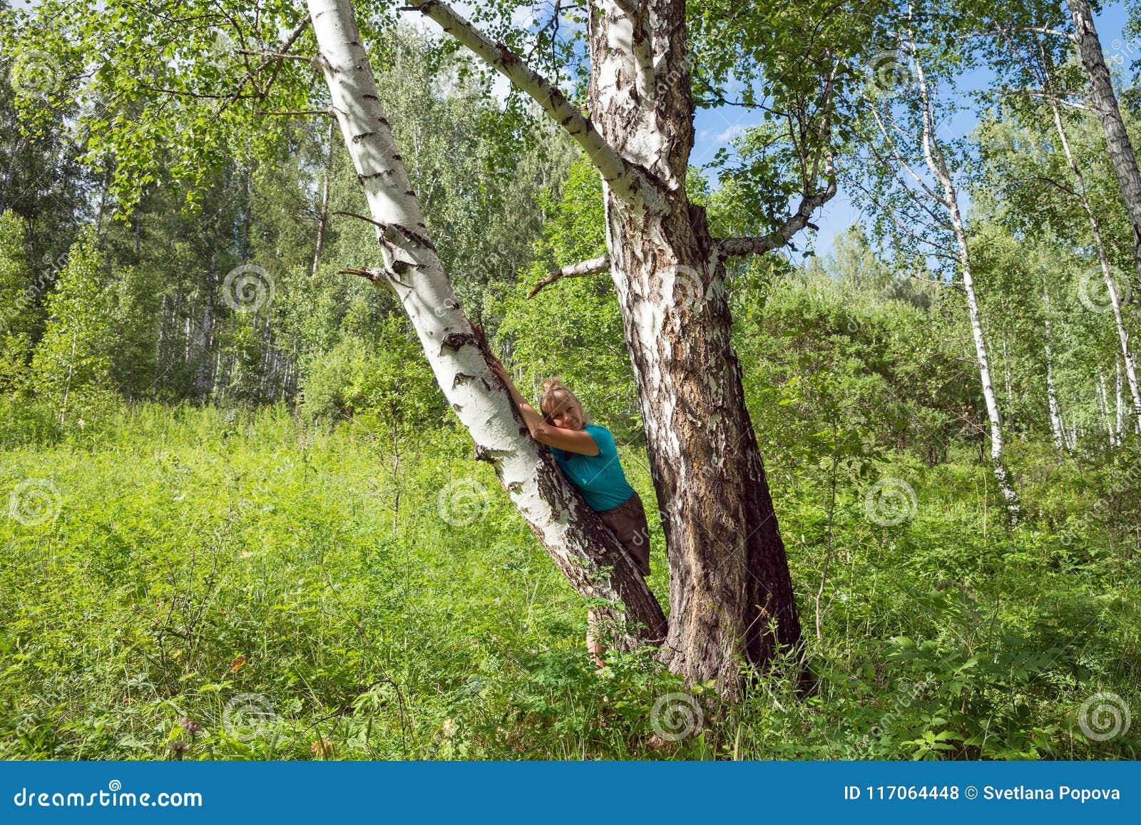 Средн-постаретая женщина положилась против дерева березы в лесе
