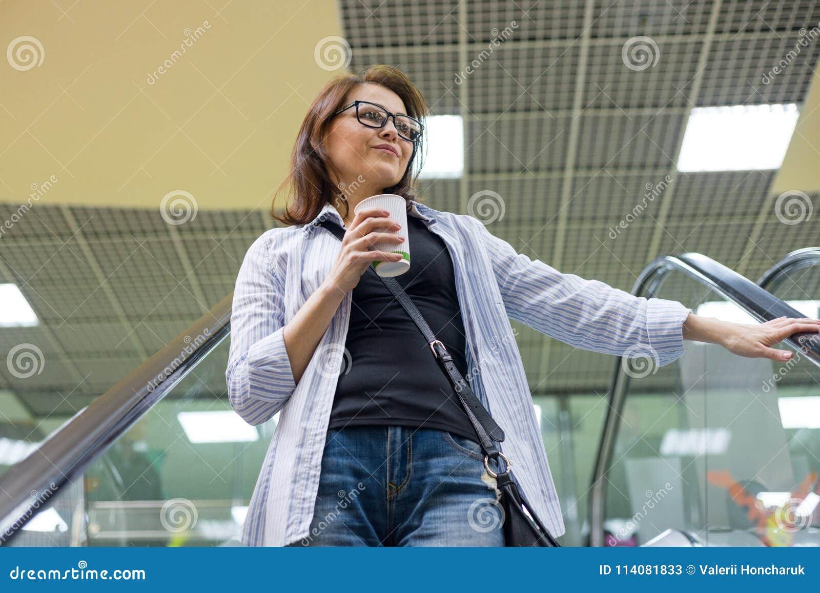 Средн-постаретая женщина с чашкой кофе, развлекательным центром торгового центра предпосылки Образ жизни, отдых и концепция людей