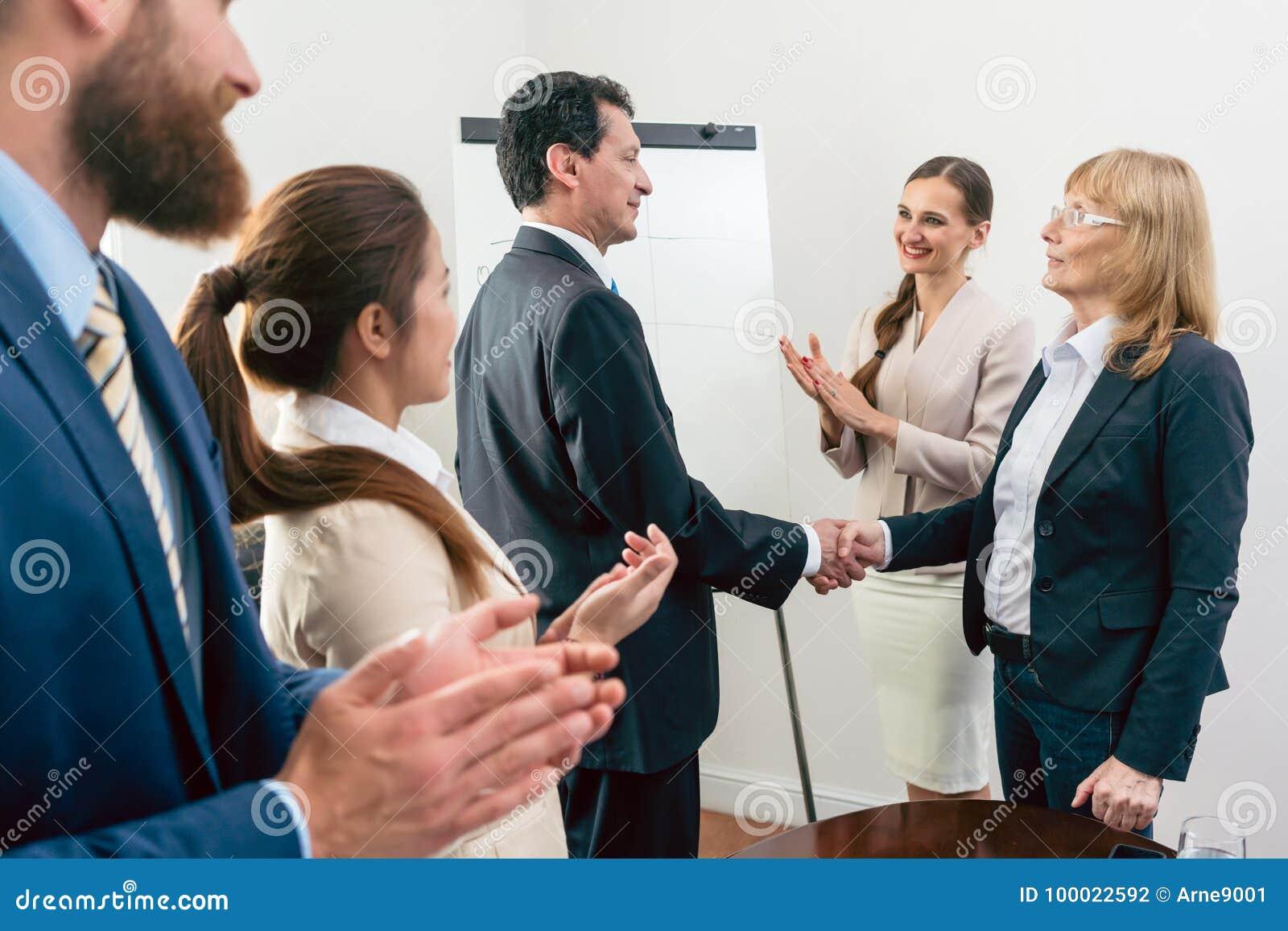 2 средн-постаретых бизнес-партнера усмехаясь пока трясущ руки