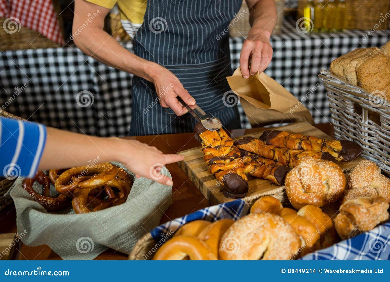 Средний раздел штата пакуя сладостную еду в бумажной сумке на счетчике
