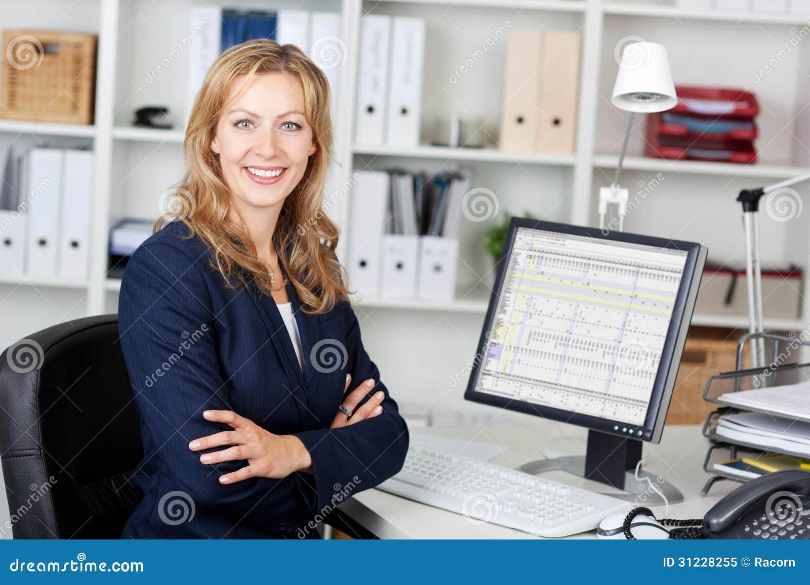 Средняя взрослая коммерсантка с компьютером на столе