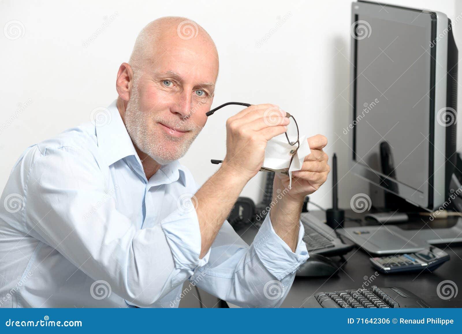 Средн-постаретый человек очищает его стекла в его офисе