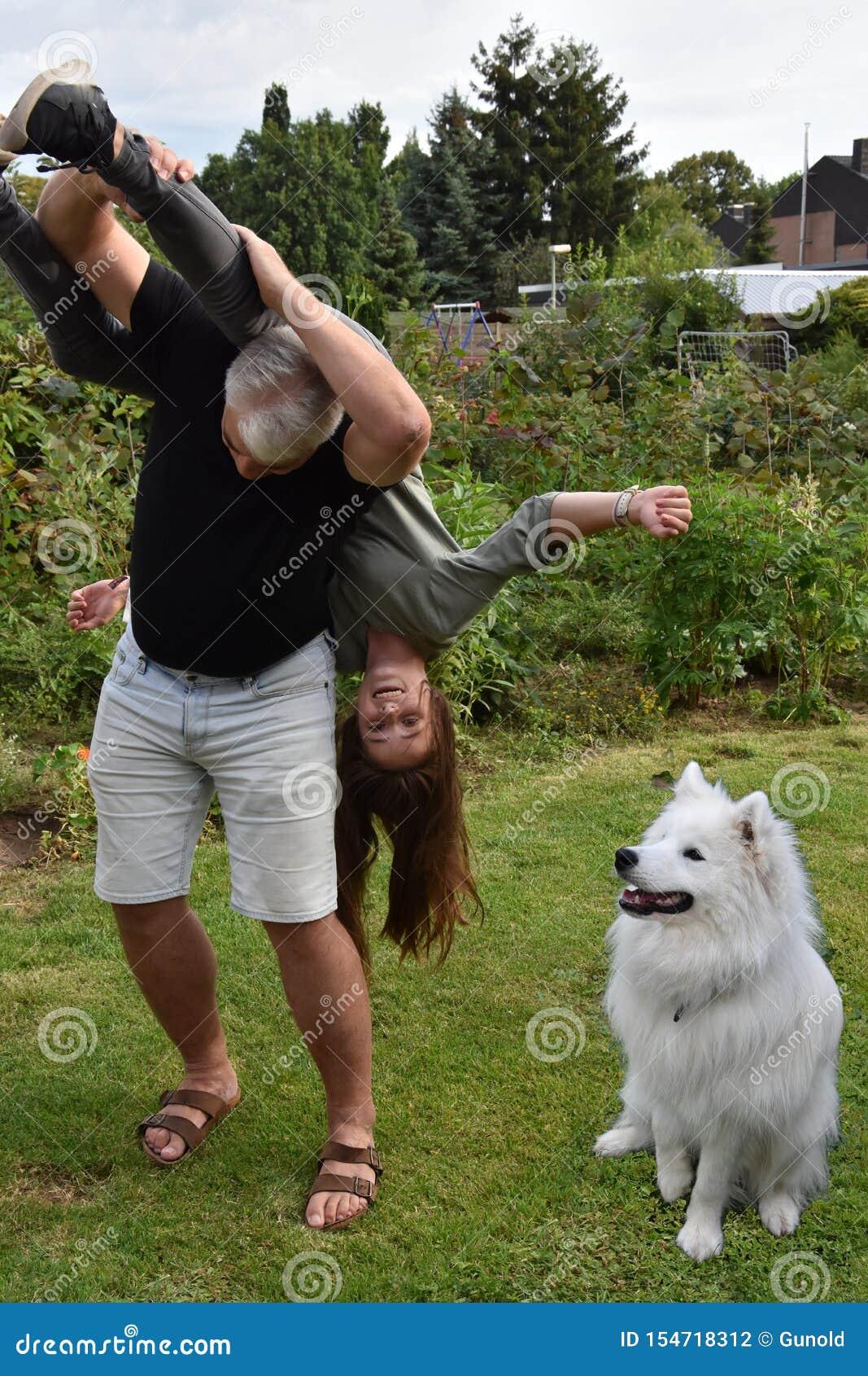 Ссорясь отец и дочь, собака наблюдают удивленный