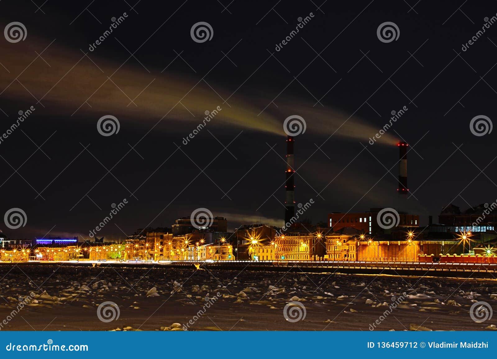 Станция тепловой мощности ночи зимы на обваловке реки Neva в Санкт-Петербурге