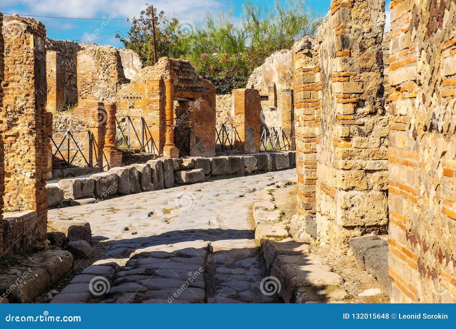 Старая вымощенная улица взята в середине римских руин в Помпеи, Италии