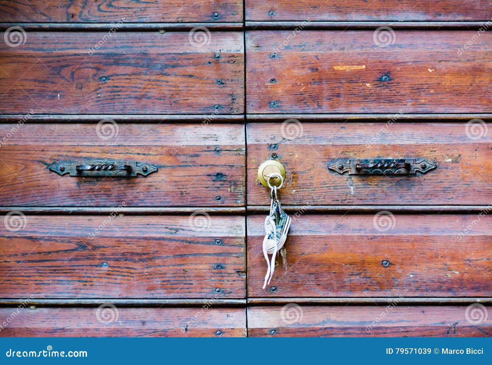 Старая деревянная дверь при ключевые цепи вися на двери