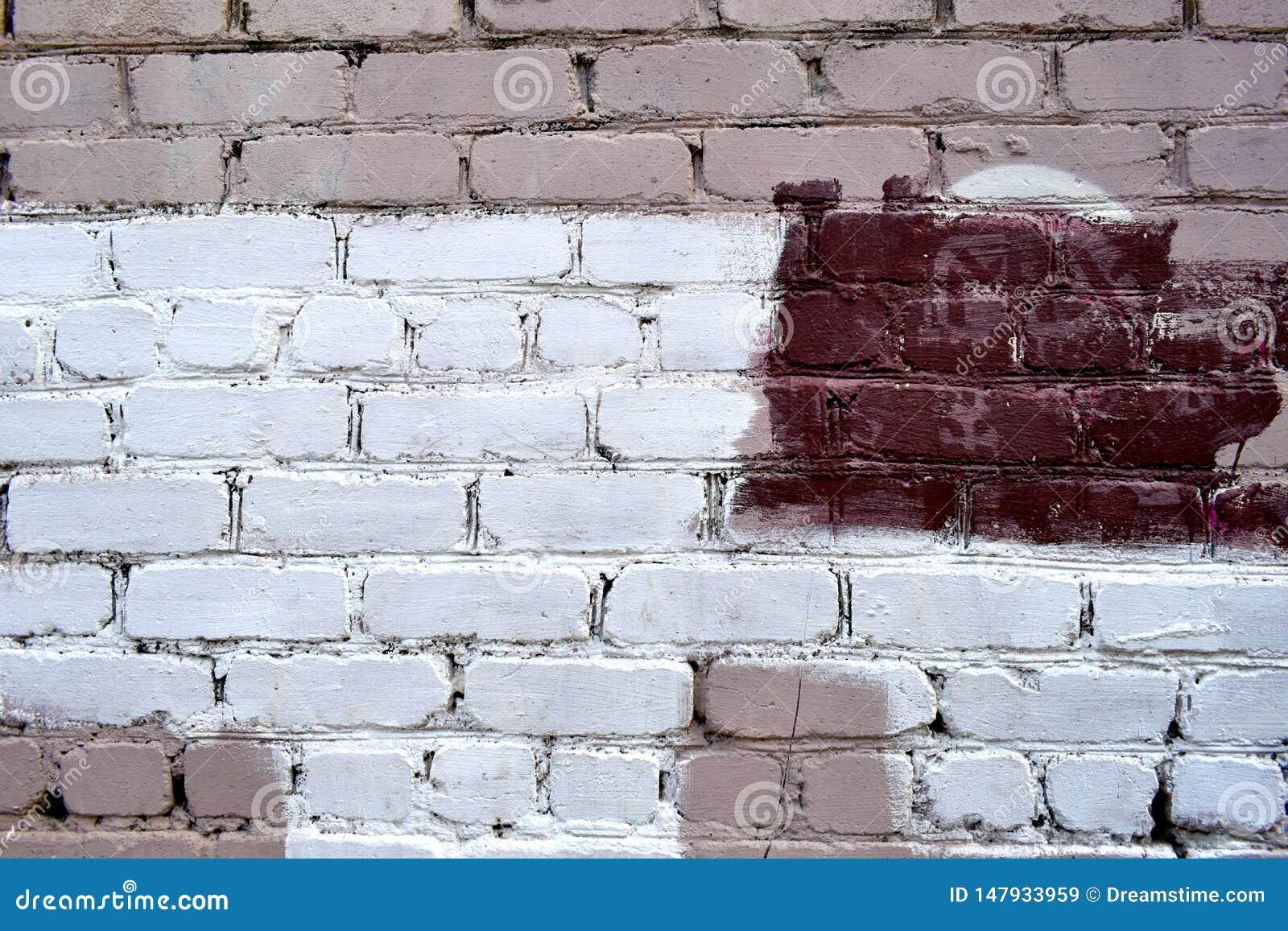 Старая кирпичная стена с белыми и красными пятнами краски
