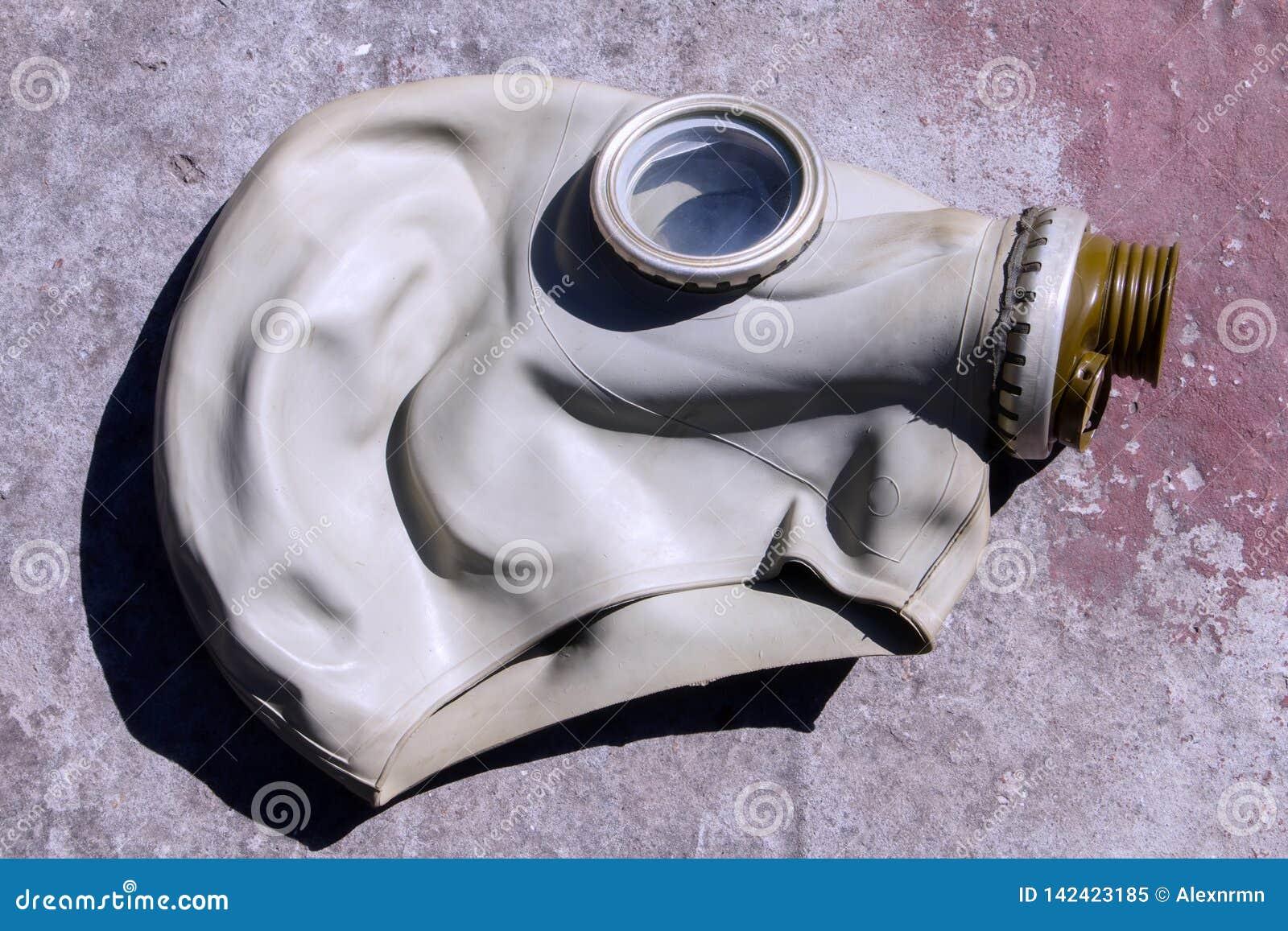 Старая маска противогаза на бетонной плите