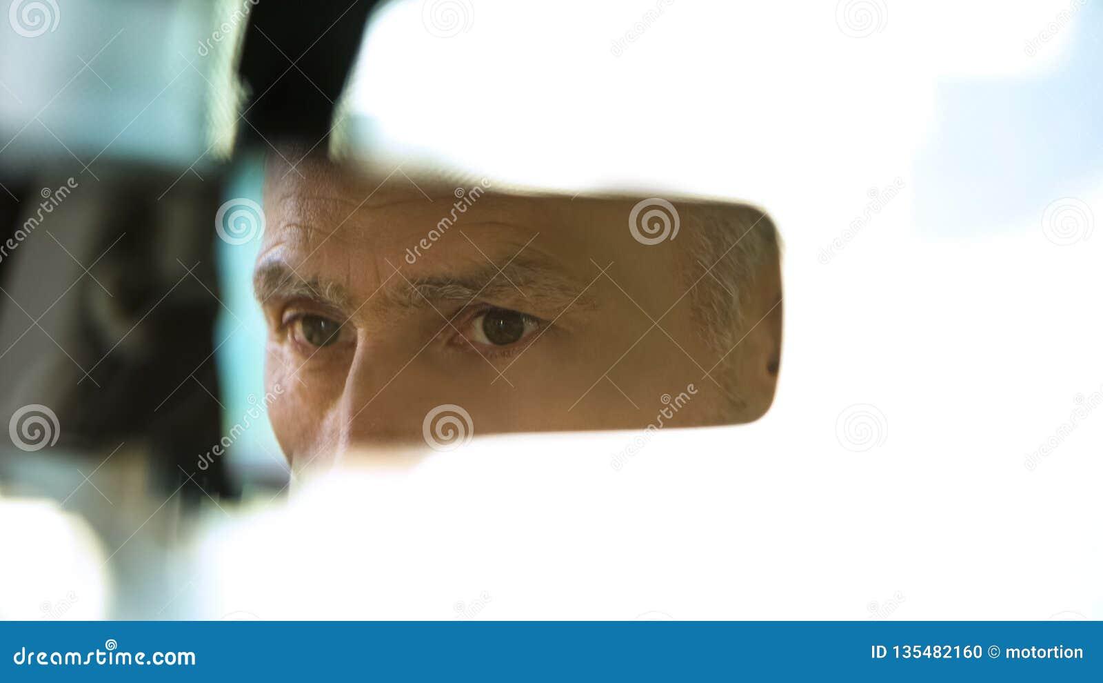 Старая мужская сторона отражая в зеркале заднего вида, водителе такси, безопасности дорожного движения, автомобиле