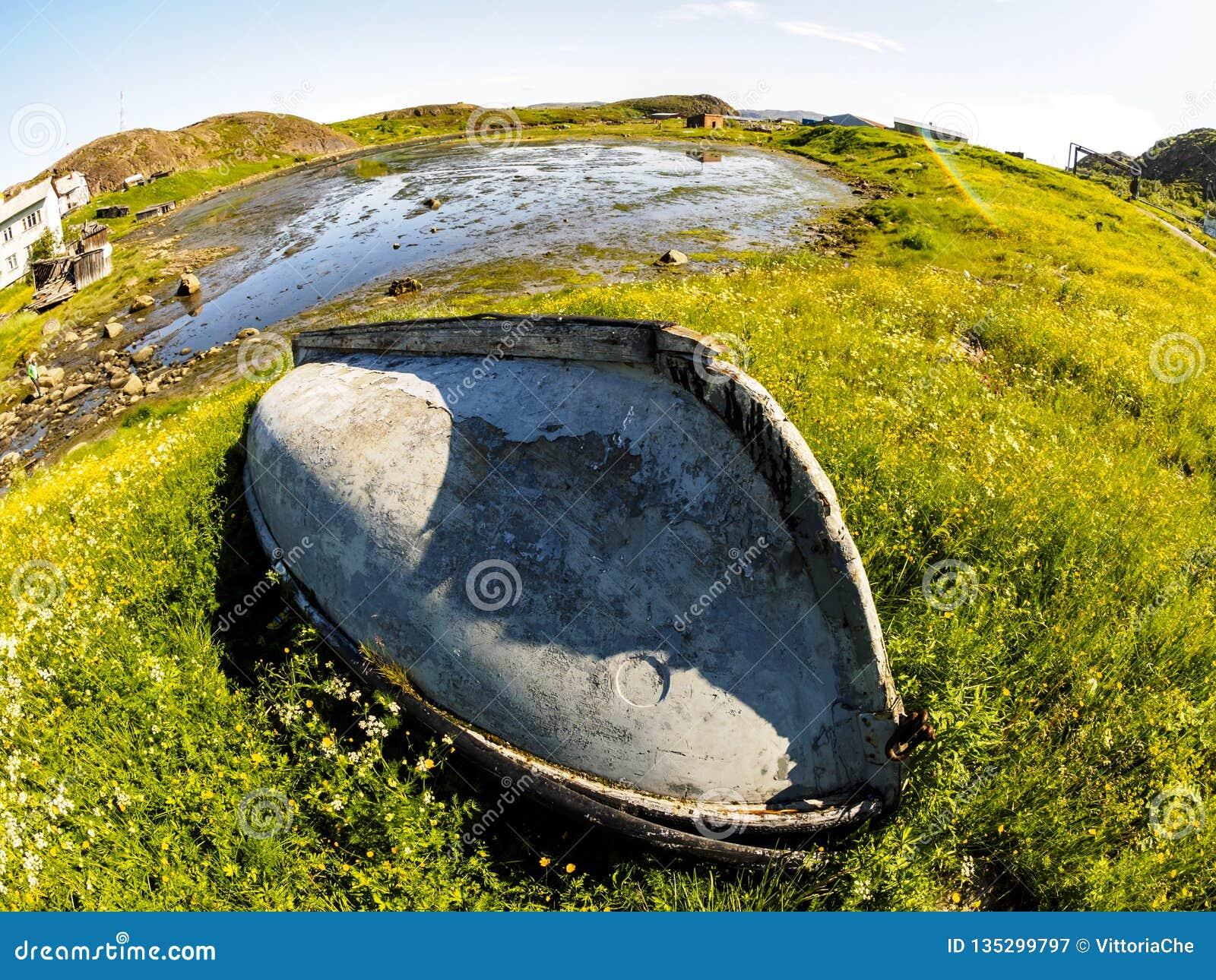 Старая получившаяся отказ шлюпка в деревне Teriberka, полуострове Kola, России