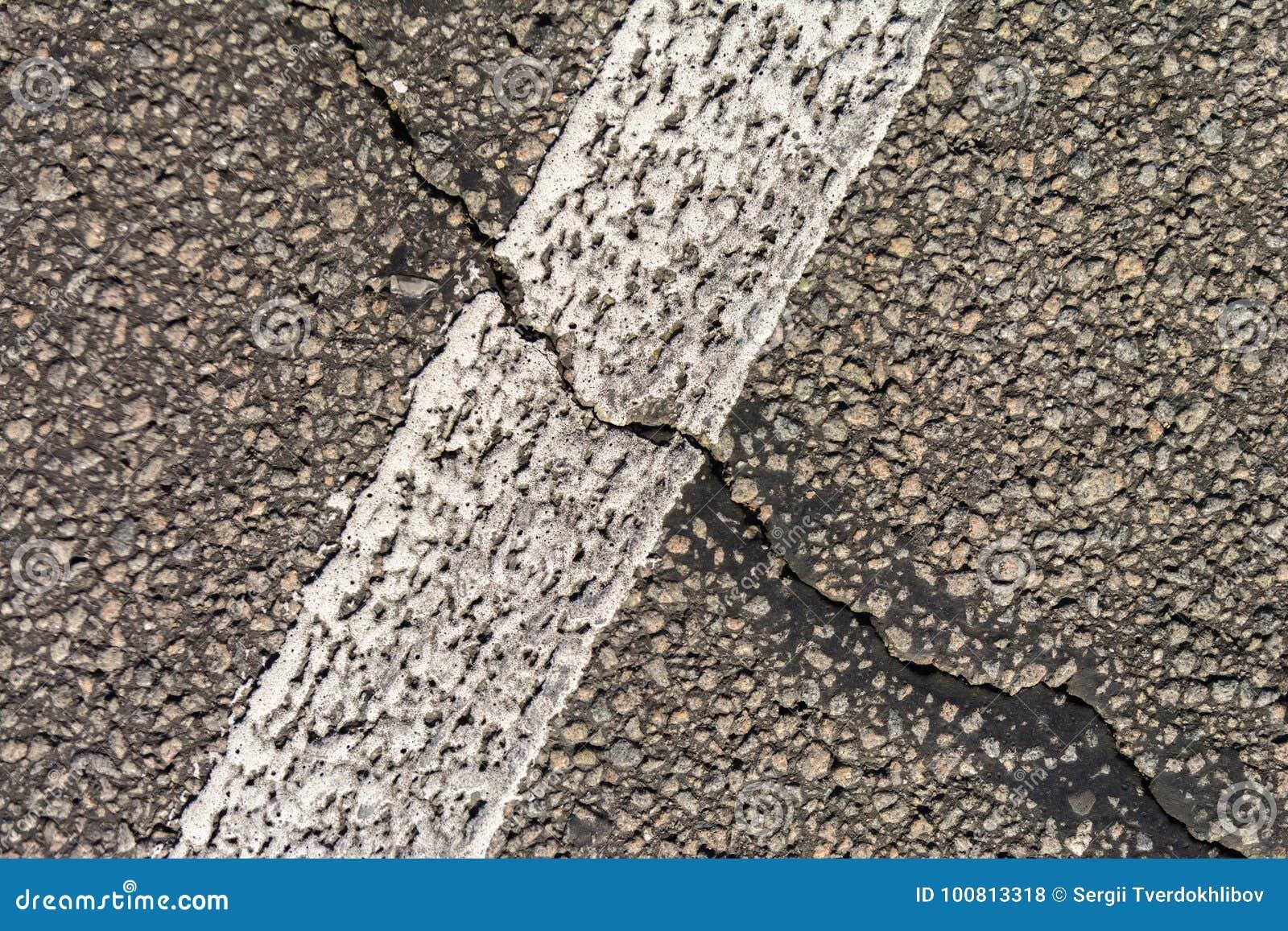 Старая треснутая дорога асфальта Белые маркировки на дороге Отремонтируйте требует скопируйте космос