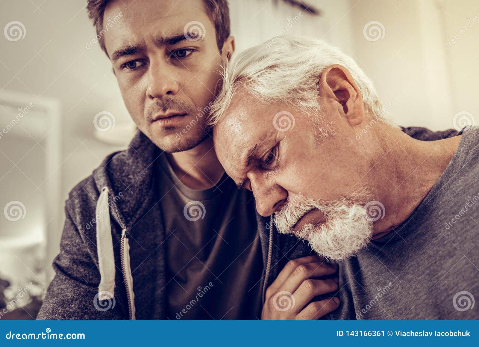 Старея голова склонности человека на плече его сына