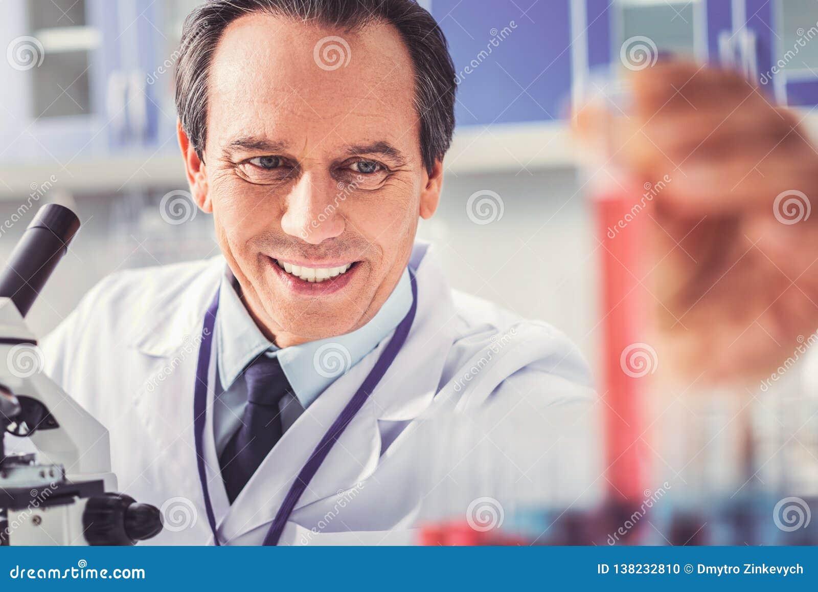 Старея химик с морщинками делая новый отчет